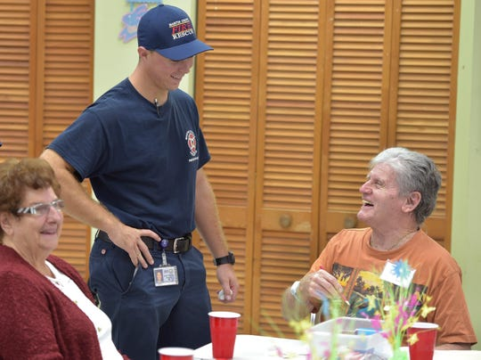 """Martin County Fire Rescue firefighter/EMT Evan Travers (center) socializes with Dominic Cafarella (right), a patient at the Alzheimer's Community Care Specialized Adult Care Center on Wednesday, March 20, 2019, at the Prince of Peace Lutheran Church in Stuart. Martin County Fire Rescue visited the center to distribute Martin County HUGS window clings to patients, which could help first responders identify homes where a person living with dementia resides. """"I love helping people,"""" Travers said."""
