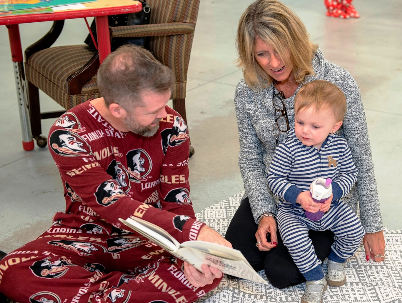 Guest readers Jeff Shearer, left, and Gigi Suntum share a story with a child at the Pajama Jam to benefit The Language & Literacy Connection. Shearer is CEO of Tykes & Teens. Suntum is executive director of Caring Children Clothing Children.