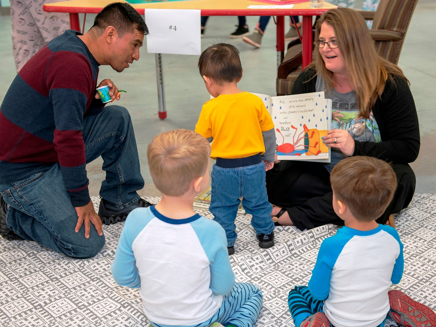 Guest reader Erin Russell, right, director of Global Learning Preschool, shows a book to children at the Pajama Jam.