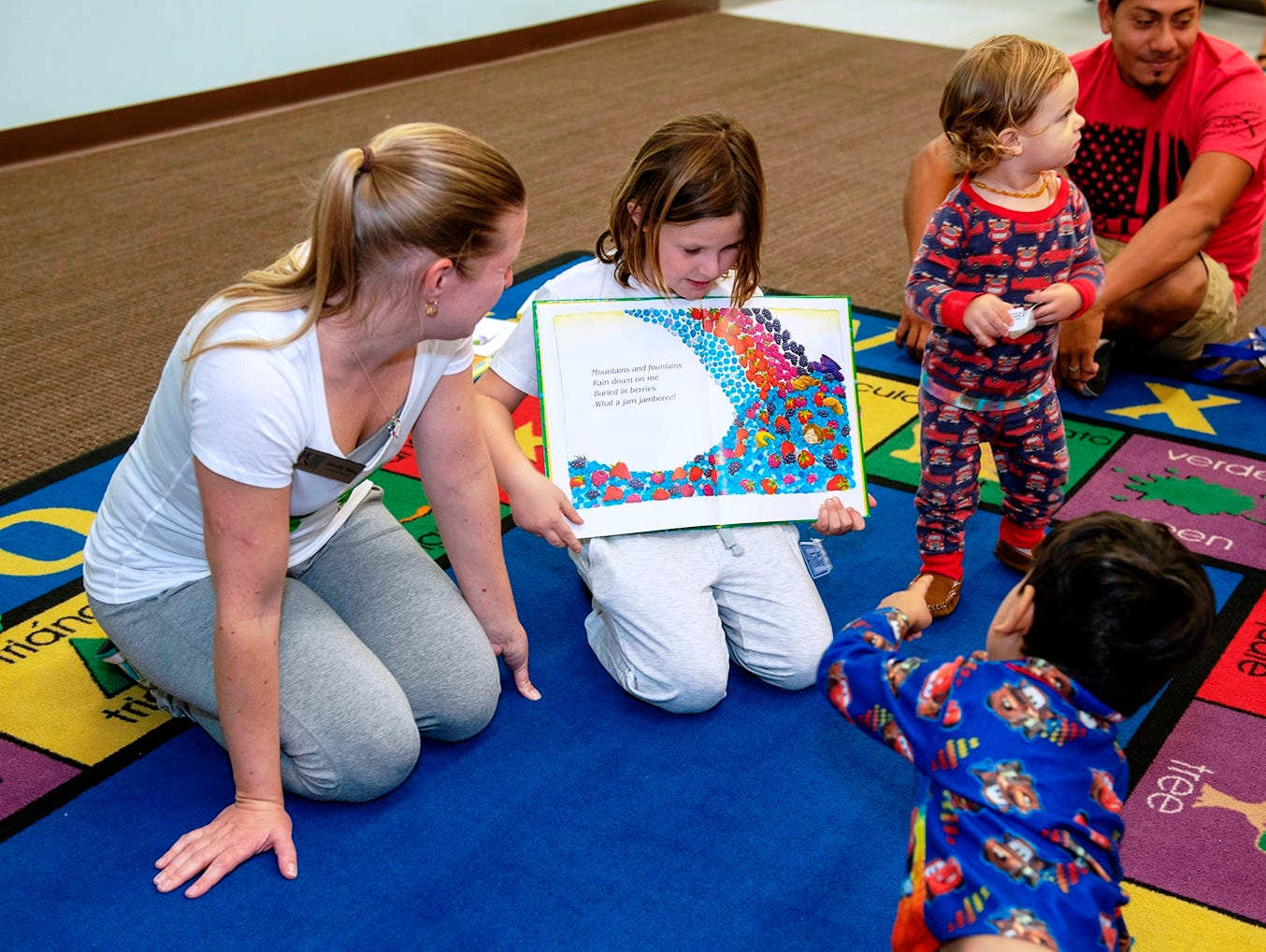 Guest reader Jennifer Salas, left, director of the Martin County Library System, at the Pajama Jam to benefit The Language & Literacy Connection.