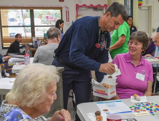 """Martin County firefighter/paramedic Scott Neumann (center) offers donuts to Mona Dexter, a patient at the Alzheimer's Community Care Specialized Adult Care Center, on Wednesday, March 20, 2019, as Martin County Fire Rescue members visit the center to distribute Martin County HUGS window clings to the patients. """"These people need a lot more assistance than most so anytime we can help out we love to do it,"""" Neumann said."""