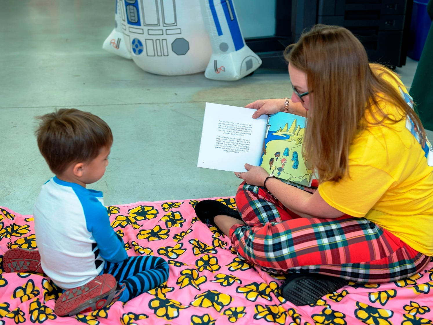 Guest reader Lisa Soesbe, author of children's books, reads to a child at the Pajama Jam.