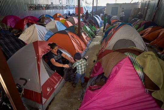 In this March 5, 2019, image, Ruth Aracely Monroy helps her son, Carlos, with his jacket among tents set up inside a shelter for migrants in Tijuana, Mexico. After fleeing violence in El Salvador and requesting asylum in the United States, the family was returned to Tijuana to wait for their hearing in San Diego. They became one of the first families to contend with a new policy that makes asylum seekers stay in Mexico while their cases wind through U.S. immigration courts. (AP Photo/Gregory Bull)