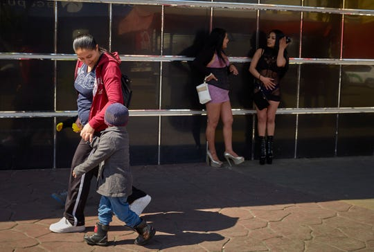 In this March 5, 2019, image, Ruth Aracely Monroy walks with her sons as they pass two women in the red-light district of Tijuana, Mexico. (AP Photo/Gregory Bull)