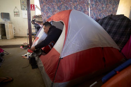 """In this March 5, 2019, image, Juan Carlos Perla looks out from the family's tent - a two-person tent where all five members of the family sleep - inside a shelter for migrants in Tijuana, Mexico. """"Our fear is that we lose our case and get deported"""" to El Salvador, he said. """"That's suicide for me, my wife and my children."""