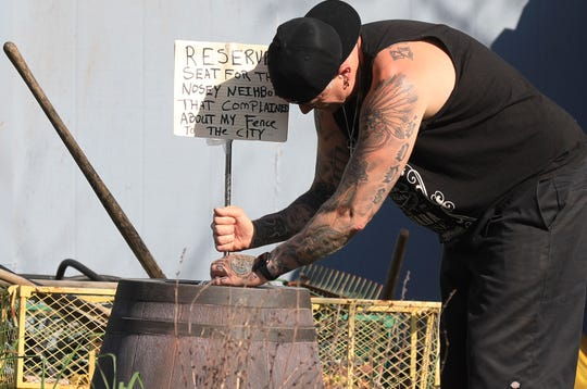 In this Monday photo, homeowner Jason Winduce attempts to keep a sign he wrote from tipping over in the wind after he set up a display of nude mannequins in his Santa Rosa yard, stemming from a neighbor's complaint to the city that a 6-foot-tall fence was a code violation. Winduce had to cut the fence to 3 feet. P)