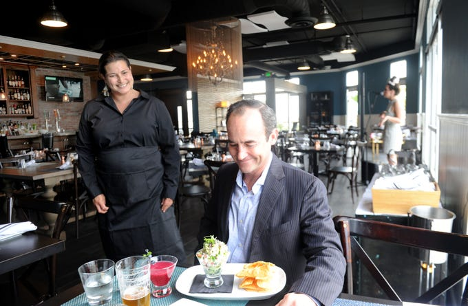 Cristina Nowling, general manager at Salt Waterside Bistro serves Eric Hanke the ceviche dish. This is the third restaurant at the Oxnard site in recent years.