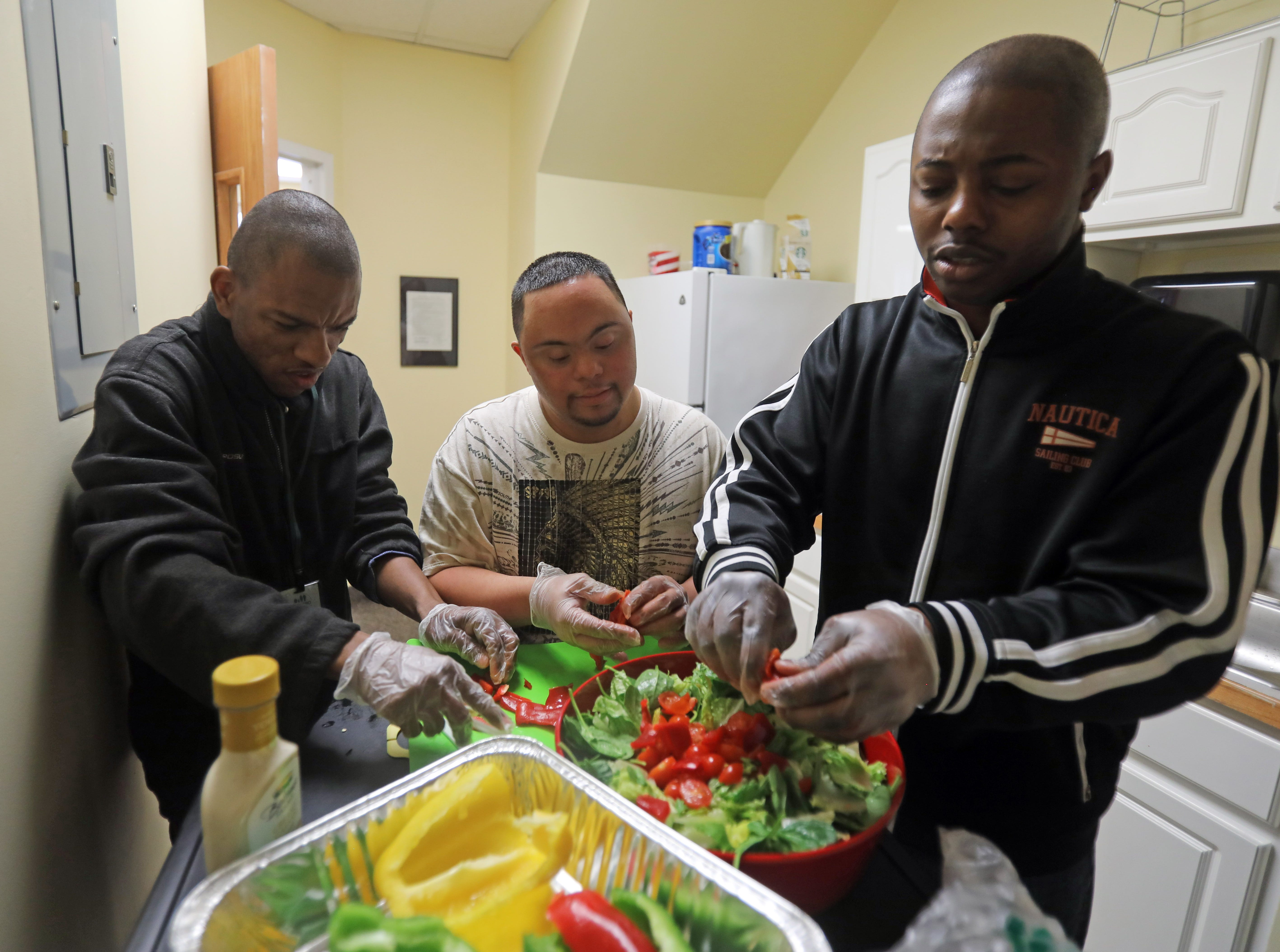 Anthony Mundy, 29, center, and his friends Sebastien Castel, left, and Tyshawn Stewartson, right, cut up veggies to put in the chicken salad that is being served for lunch during a day program atJawoniocalled Without Walls or WOW in Spring Valley March 14, 2019.