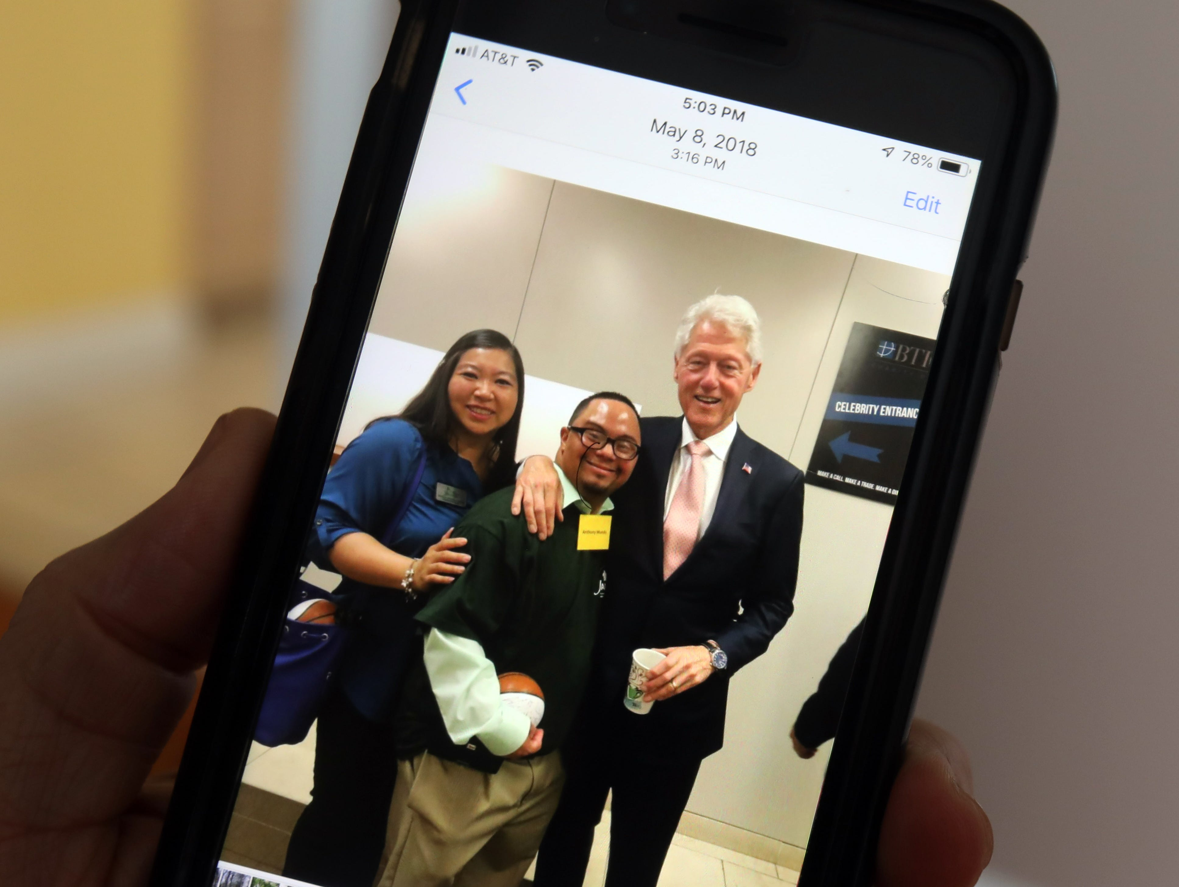 Anthony Mundy, 29 shows a photo he took with former President Bill Clinton during a charity event he attended to bring awareness to programs for adults with disabilities.