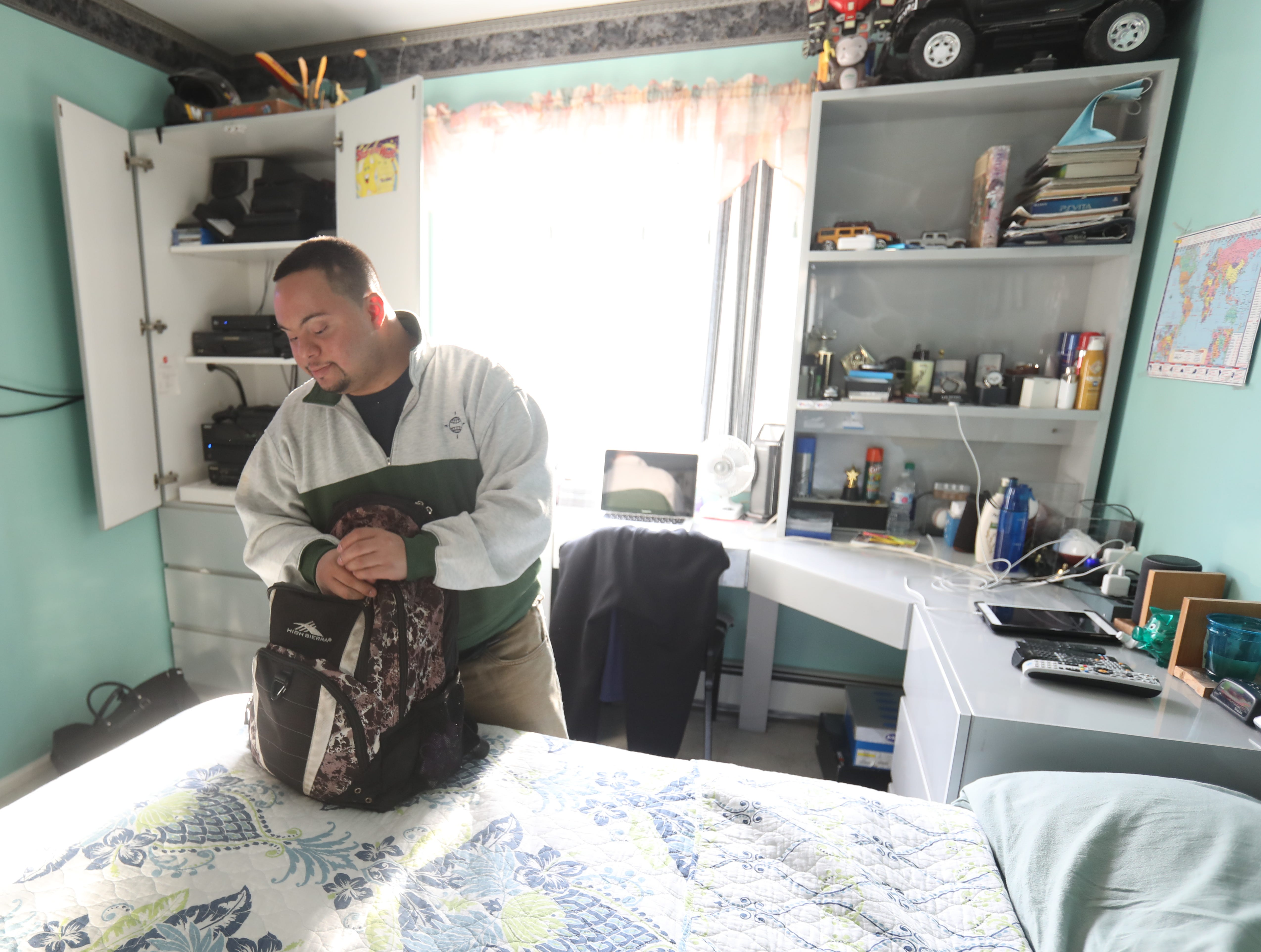 Anthony Mundy, 29 packs his bag in his bedroom in Spring Valley on March 15, 2019, before his ride picks him up for his day program at Jawano.