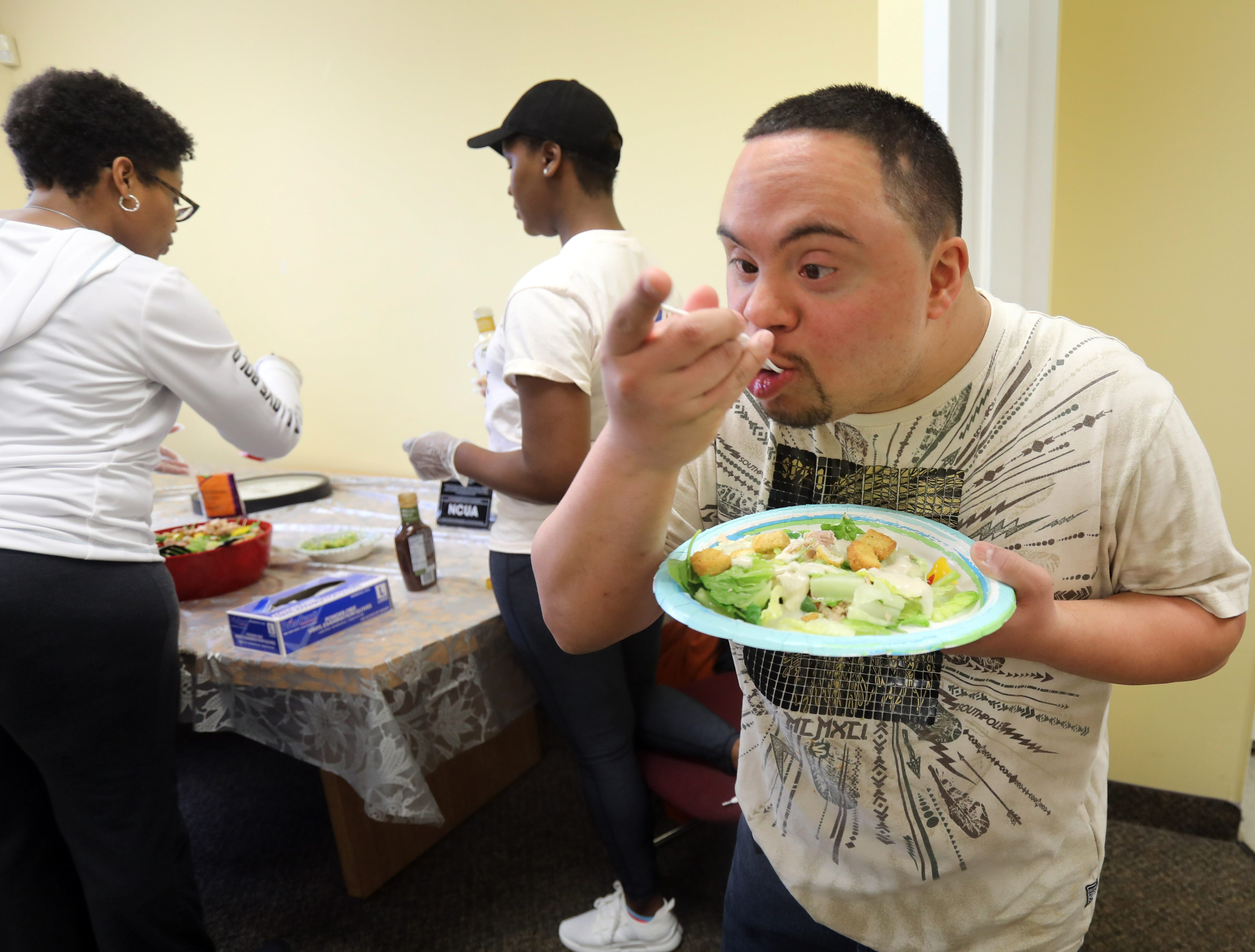 Anthony Mundy, 29 takes a bite out of the chicken salad he made for lunch during a day program atJawoniocalled Without Walls or WOW in Spring Valley March 14, 2019.