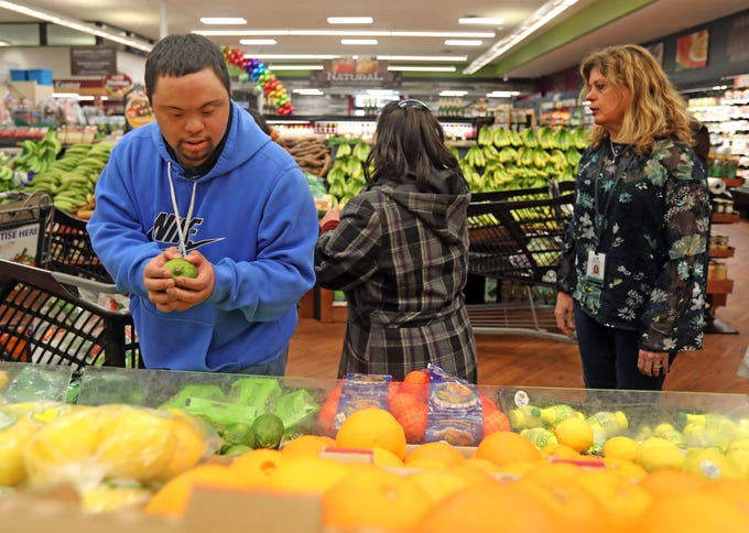 Anthony Mundy, 29 picks lemons on a shopping trip where he learns about health eating from a ShopRite dietitian in Airmont on March 12, 2019.