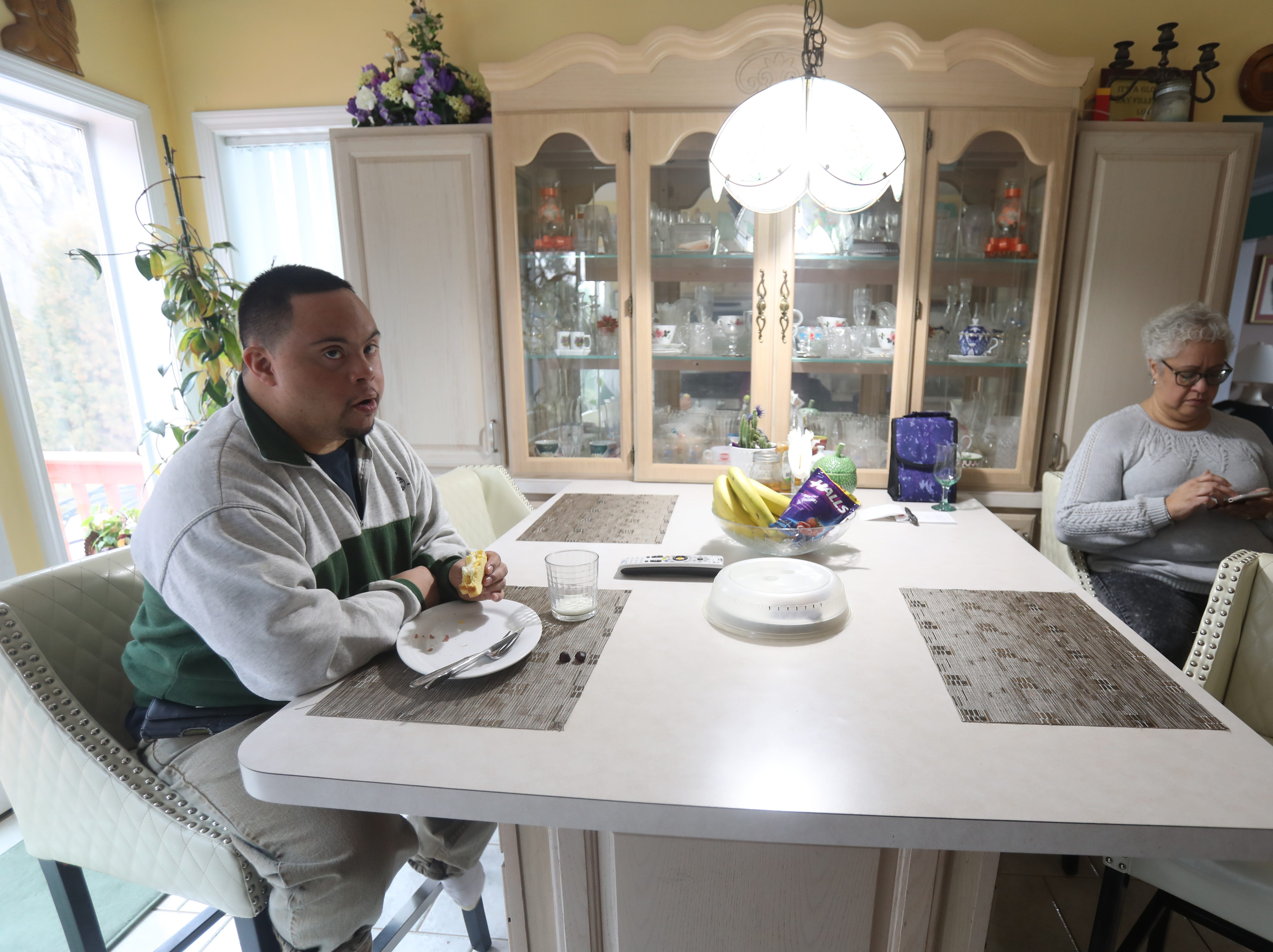 Anthony Mundy, 29 eats breakfast with his mother, Althea at home in Spring Valley on March 15, 2019, before going to his day program at Jawonio called Without Walls.