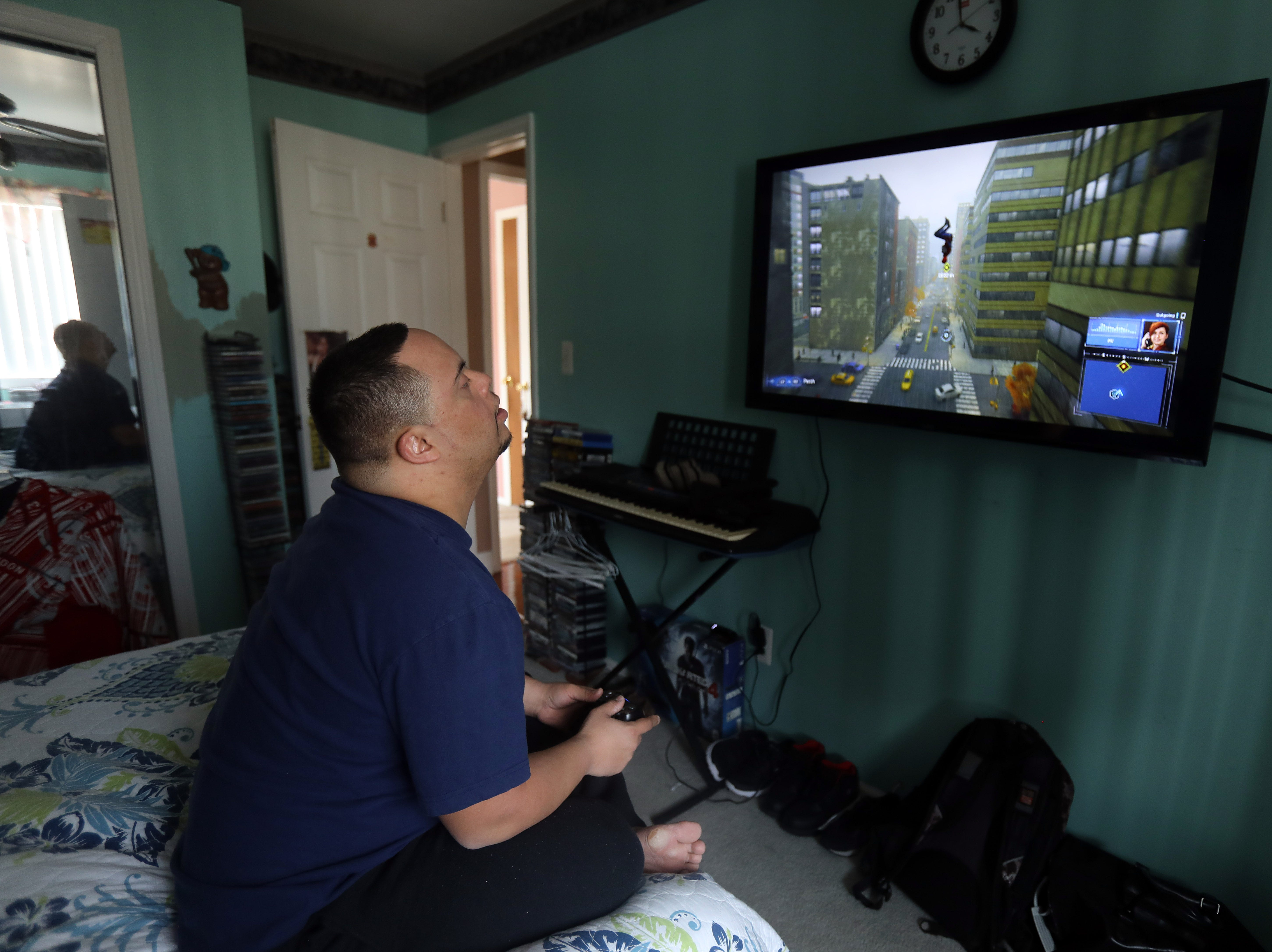 Anthony Mundy, 29 plays Spider-Man on his Playstation 4 in his bedroom in Spring Valley March 15, 2019.