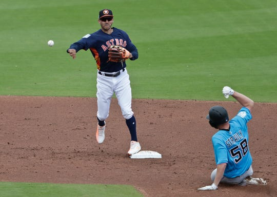 Houston Astros shortstop Carlos Correa (1) tags out Miami Marlins Dan Straily (58) for a double play during an exhibition spring training baseball game Thursday, March 14, 2019, in West Palm Beach Fla. (AP Photo/Brynn Anderson)