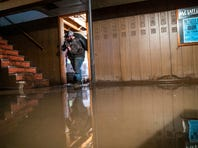 Jake Nebuda removes damaged items from the basement of home Tuesday, March 19, 2019, in North Bend, Neb. The home had over 40 inches of water in it early this week.