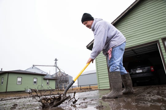 Mike Loeffler clears mud from his driveway on Willow Street while dealing with the aftermath of major flooding Tuesday, March 19, 2019, in North Bend, Neb.  The president of the Nebraska Farm Bureau says farm and ranch losses due to the devastating flooding could reach $1 billion in the state