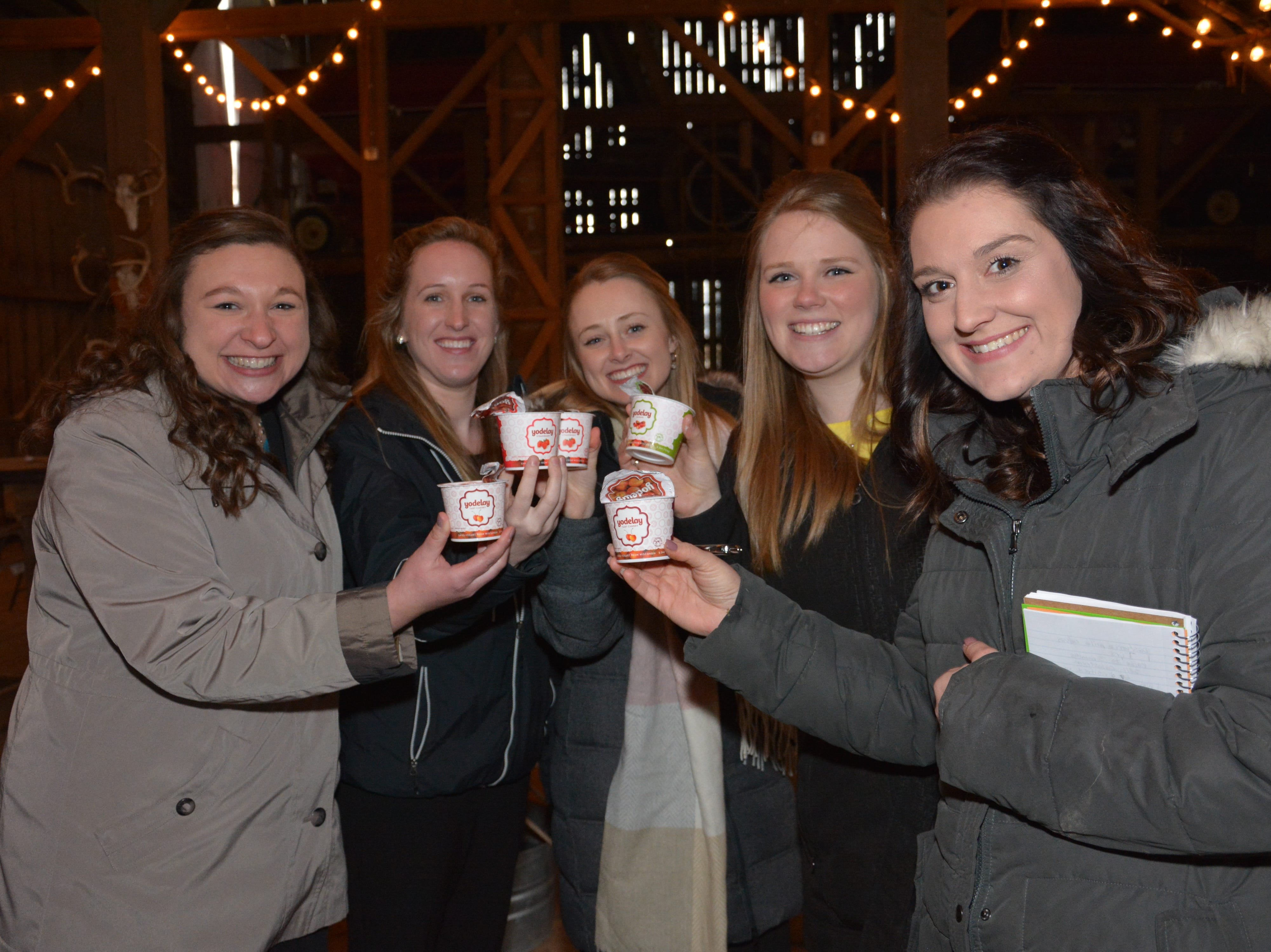 Alice in Dairyland contestants hold up containers of Yodelay Swiss-style yogurt that is made with the milk from the Voegeli family's Brown Swiss cows.
