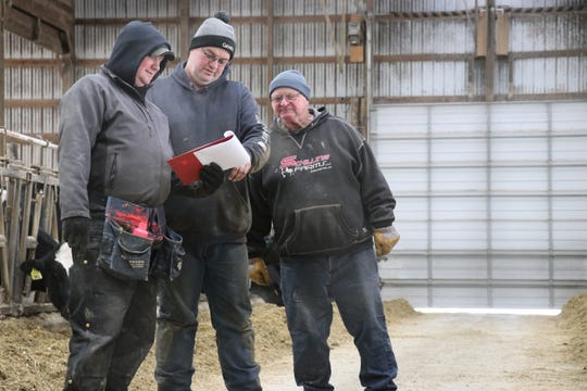 Brothers Brian Schilling (left) and his brother, Andy, along with their father, Bill, pay close attention to the production of their dairy herd.