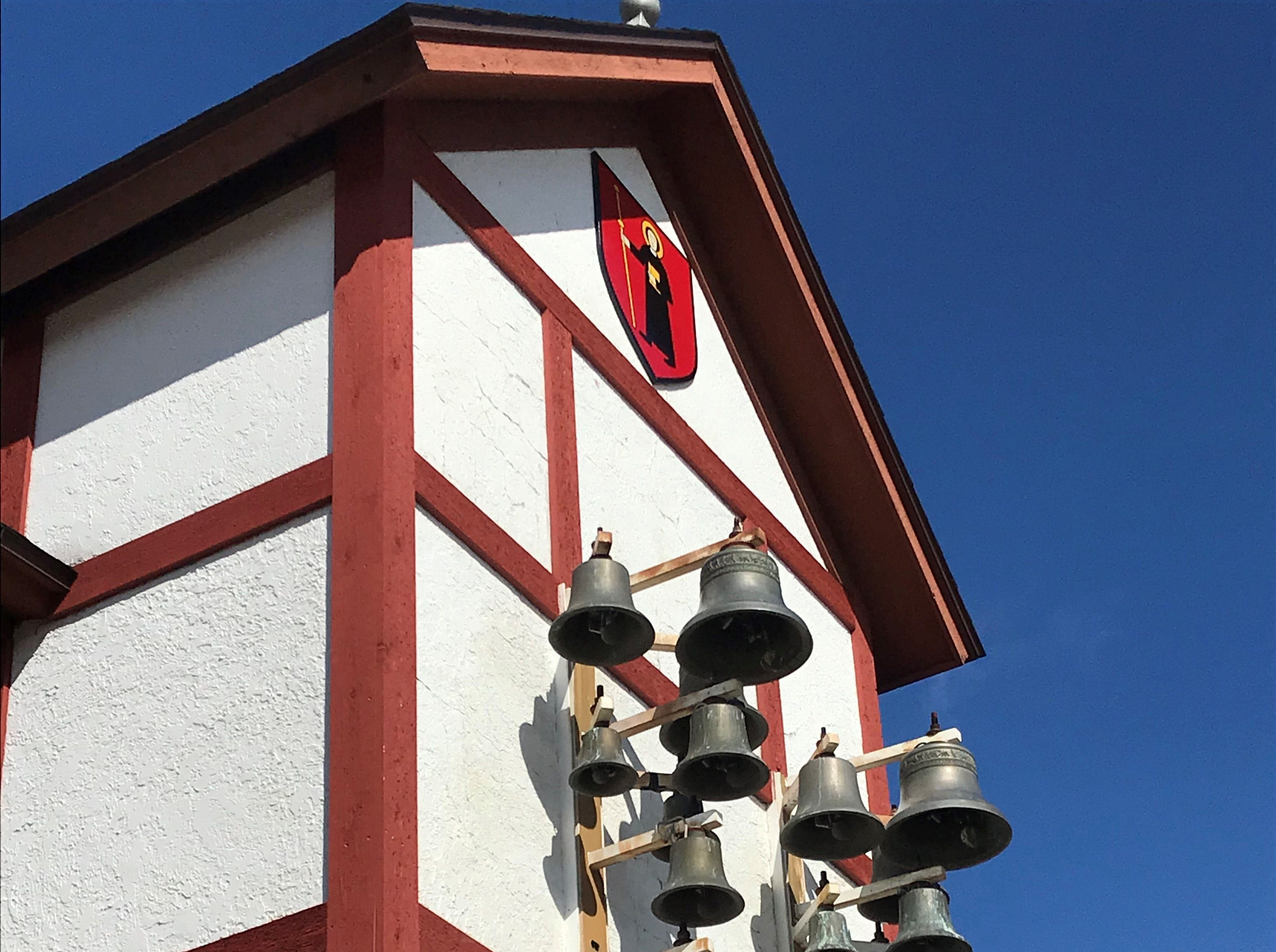 A set of bells hangs under the Swiss coat of arms in downtown New Glarus.
