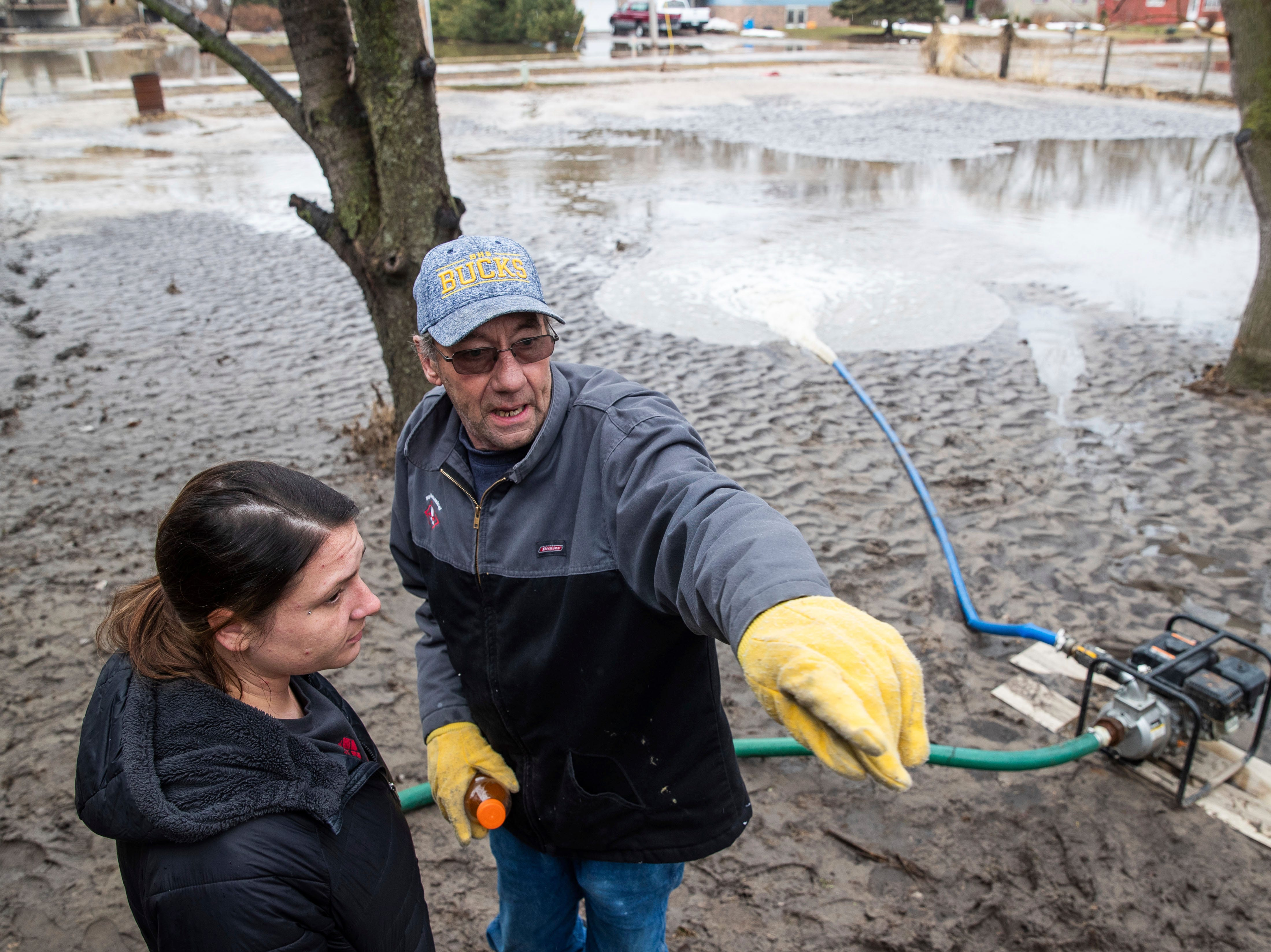 Brian Pemberton talks with Linzi Baker while trying to clear water from a home Tuesday, March 19, 2019, in Inglewood, Neb. Flooding is expected throughout the week in several states as high water levels flow down the Missouri River. Swollen rivers have already breached more than a dozen levees in Nebraska, Iowa and Missouri, according to the U.S. Army Corps of Engineers.