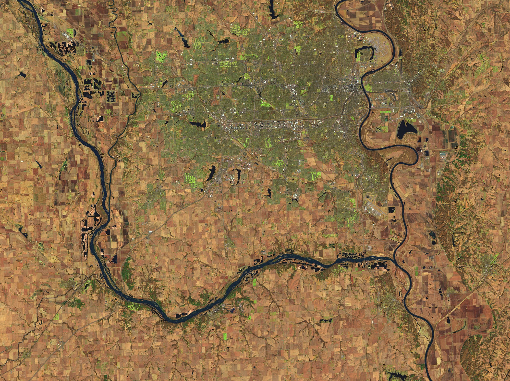 This March 20, 2018 NASA satellite image provided by NASA shows Omaha, Neb., top, surround by Platte River, left, and Mississippi River as two rivers meet just south of Offutt Air Force Base.  A disaster declaration has been declared for nearly 70 percent of the state of Nebraska. The state's Emergency Management Agency said in a news release Tuesday that 65 of the state's 93 counties are under state-issued emergency declarations.