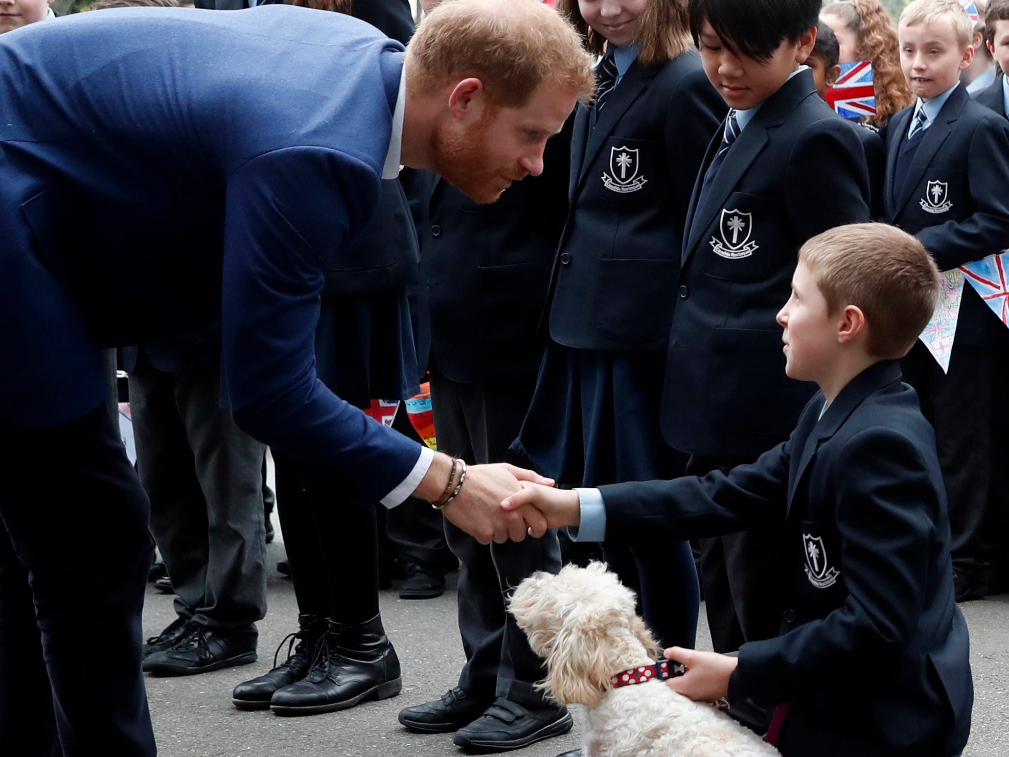 Britain's Prince Harry greets pupils from St Vincent's Catholic Primary School, along with the head teachers dog called Winnie, before going on to plant a tree from the Woodland Trust St Vincent's Catholic Primary School in Acton, in London, Wednesday, March 20, 2019. Prince Harry met the school's Eco Ambassadors, and then joined the children as they plant the saplings before planting his own tree, marking the achievements of the QCC and the Woodland Trust in providing 74,000 trees across the UK. (AP Photo/Alastair Grant, Pool) ORG XMIT: XAG120