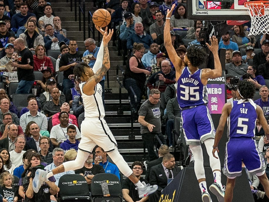 March 19: Nets guard D'Angelo Russell (1) puts up an acrobatic shot over Kings defender Marvin Bagley III (35) during the first half in Sacramento.