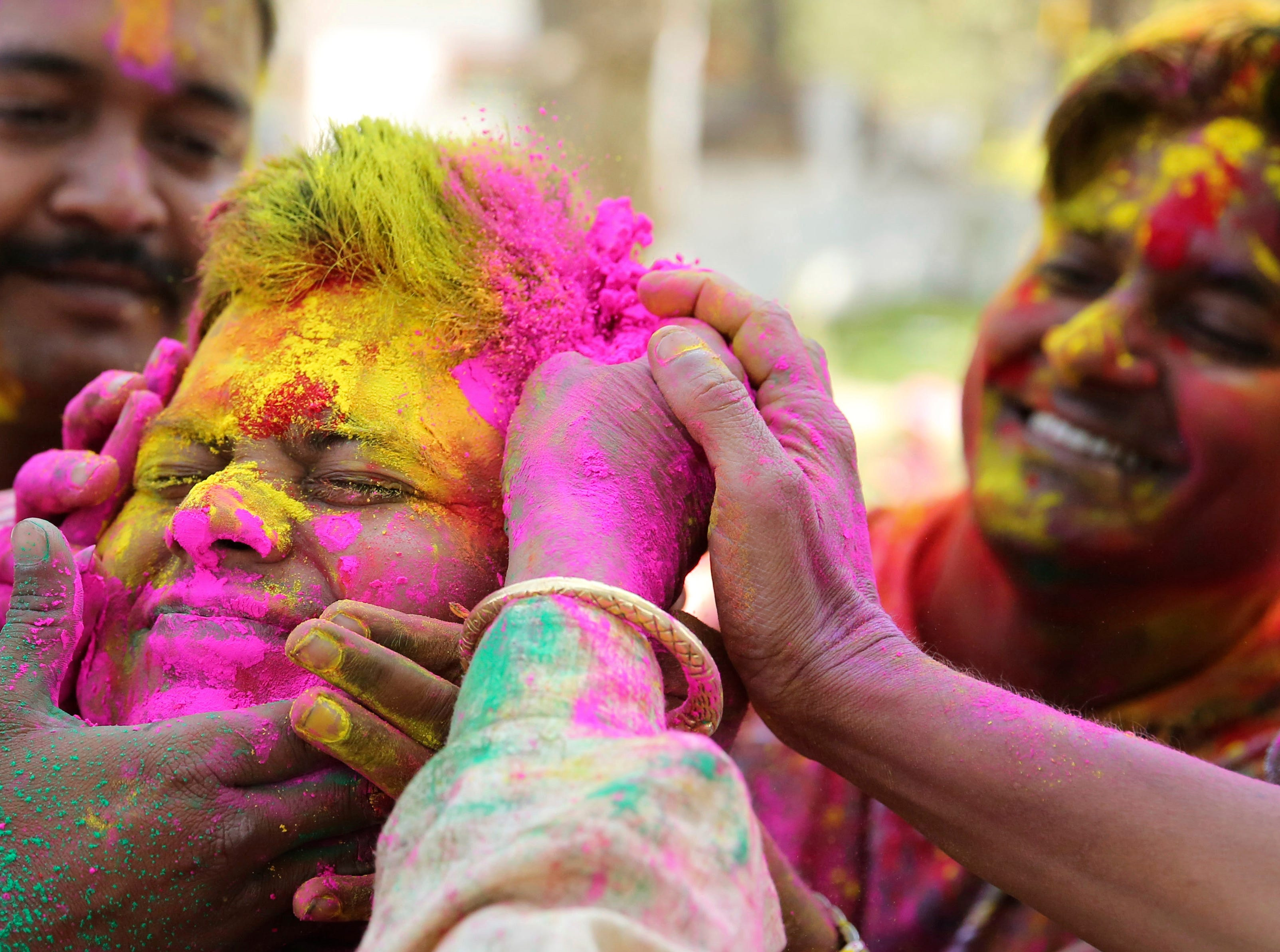 An Indian man has colored powder smeared on his face during celebrations marking Holi, the Hindu festival of colors, in Allahabad, India, Wednesday, March 20, 2019.