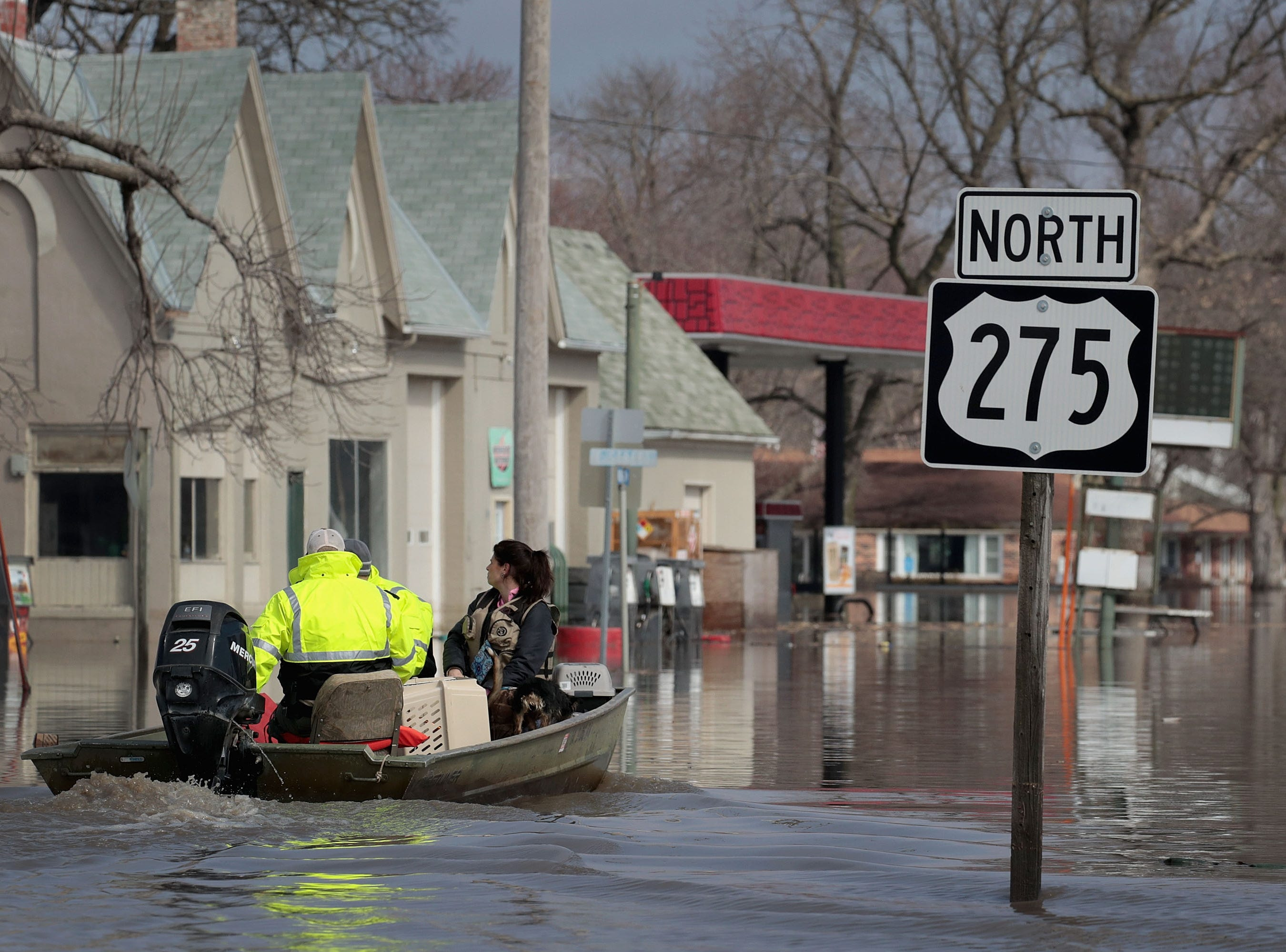 """A boater travels down a flooded street on March 20, 2019 in Hamburg, Iowa. Although flood water in the town has started to recede many homes and businesses in the town remain surrounded by water. Several Midwest states are battling some of the worst flooding they have experienced in decades as rain and snow melt from the recent """"bomb cyclone"""" has inundated rivers and streams. At least three deaths have been linked to the flooding."""