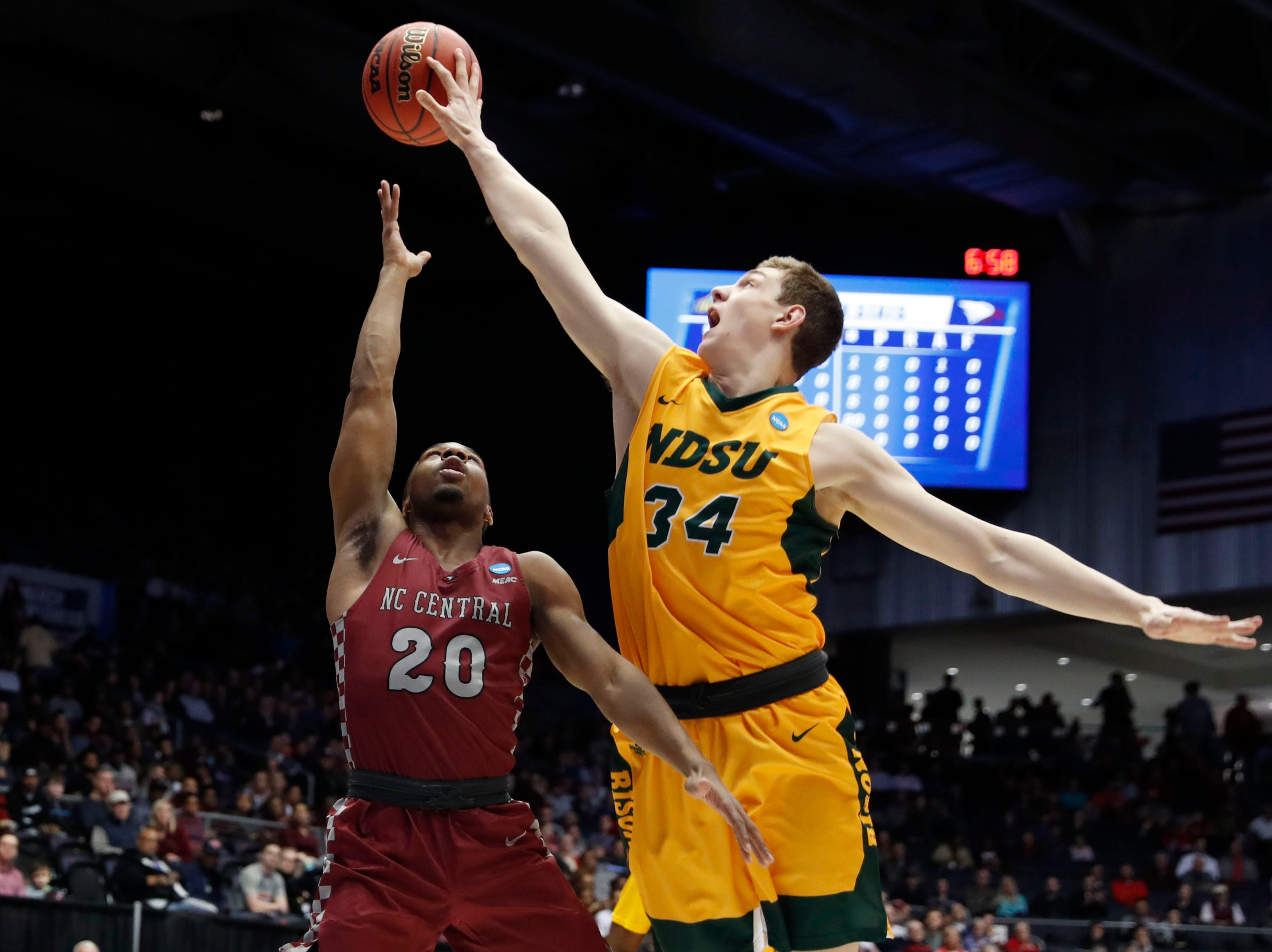 North Dakota State Bison forward Rocky Kreuser (34) blocks a shot from North Carolina Central Eagles guard Julian Walters (20) in the first half.