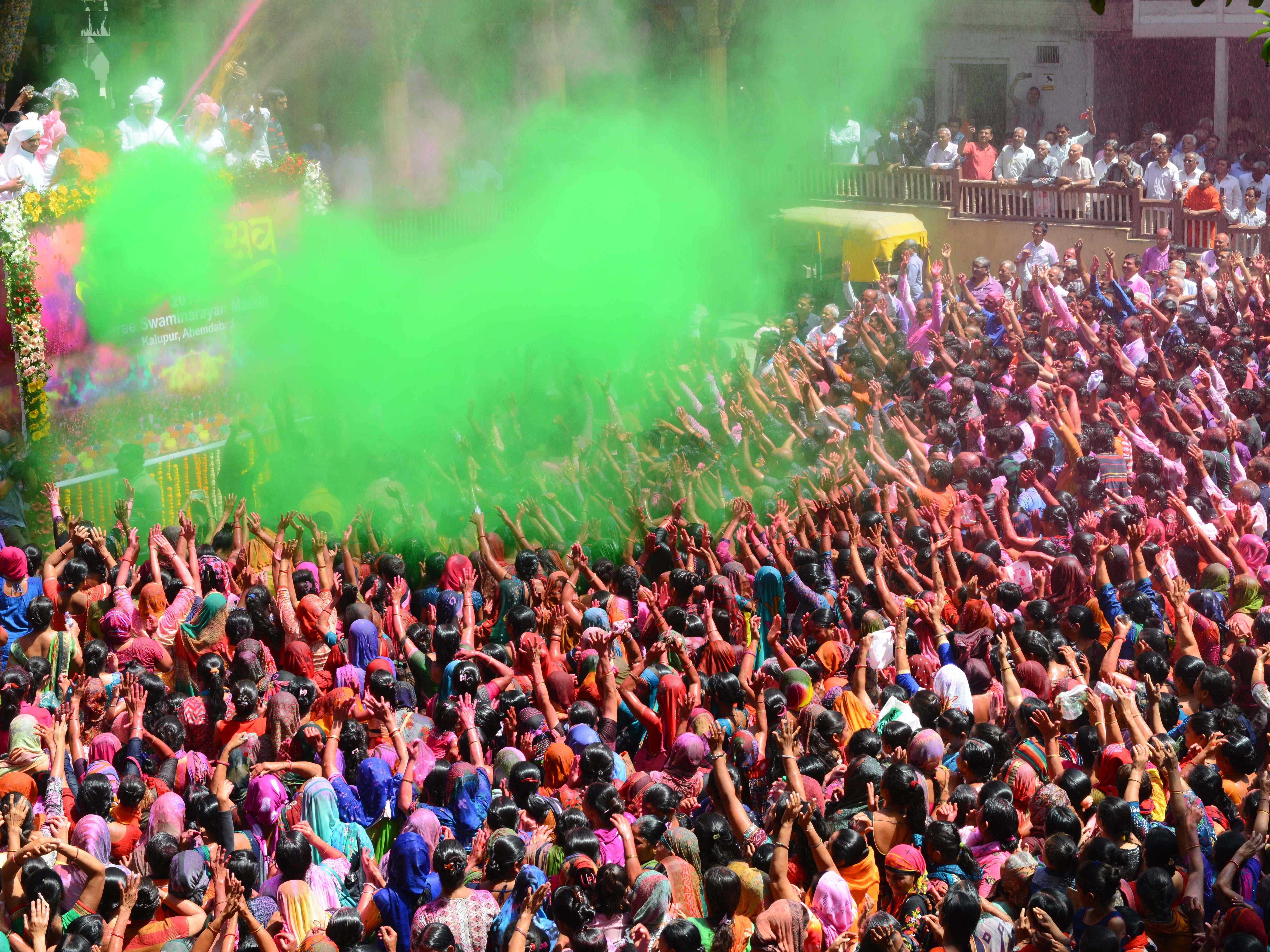 Indian Hindu devotees are sprayed with colored water as they celebrate the Holi festival at the Kalupur Swaminarayan Temple, in Ahmedabad on March 20, 2019. Holi, the popular Hindu spring festival of colors is observed in India at the end of the winter season on the last full moon of the lunar month.