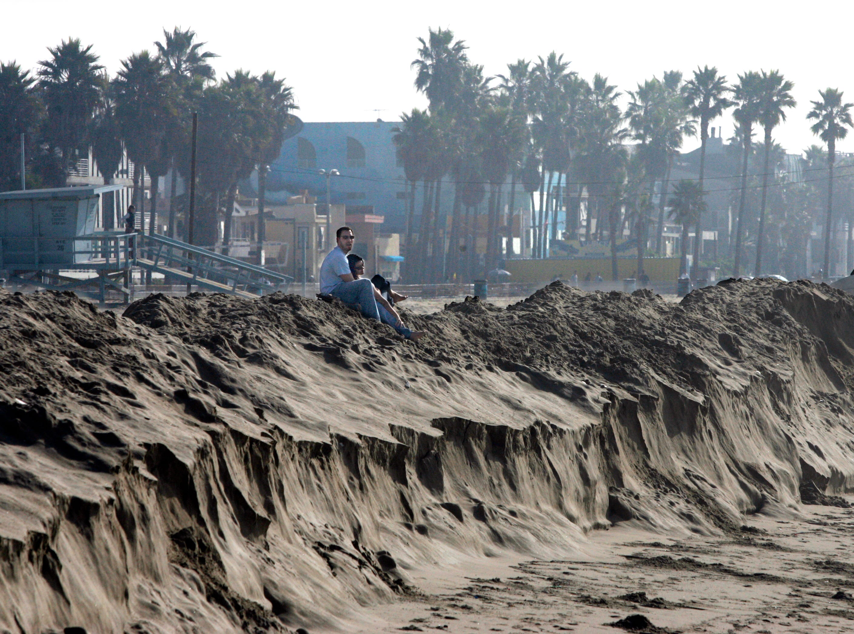 Zack Freedman, of Venice, Calif., hangs out with his girlfriend, Heather Valdez, who is visiting him from Boston, on top of an erected berm at Venice Beach, watching the surf Thursday, Dec. 29, 2005, in Los Angeles. The berm was built to protect waterfront homes and business from flooding should the surf get too big.