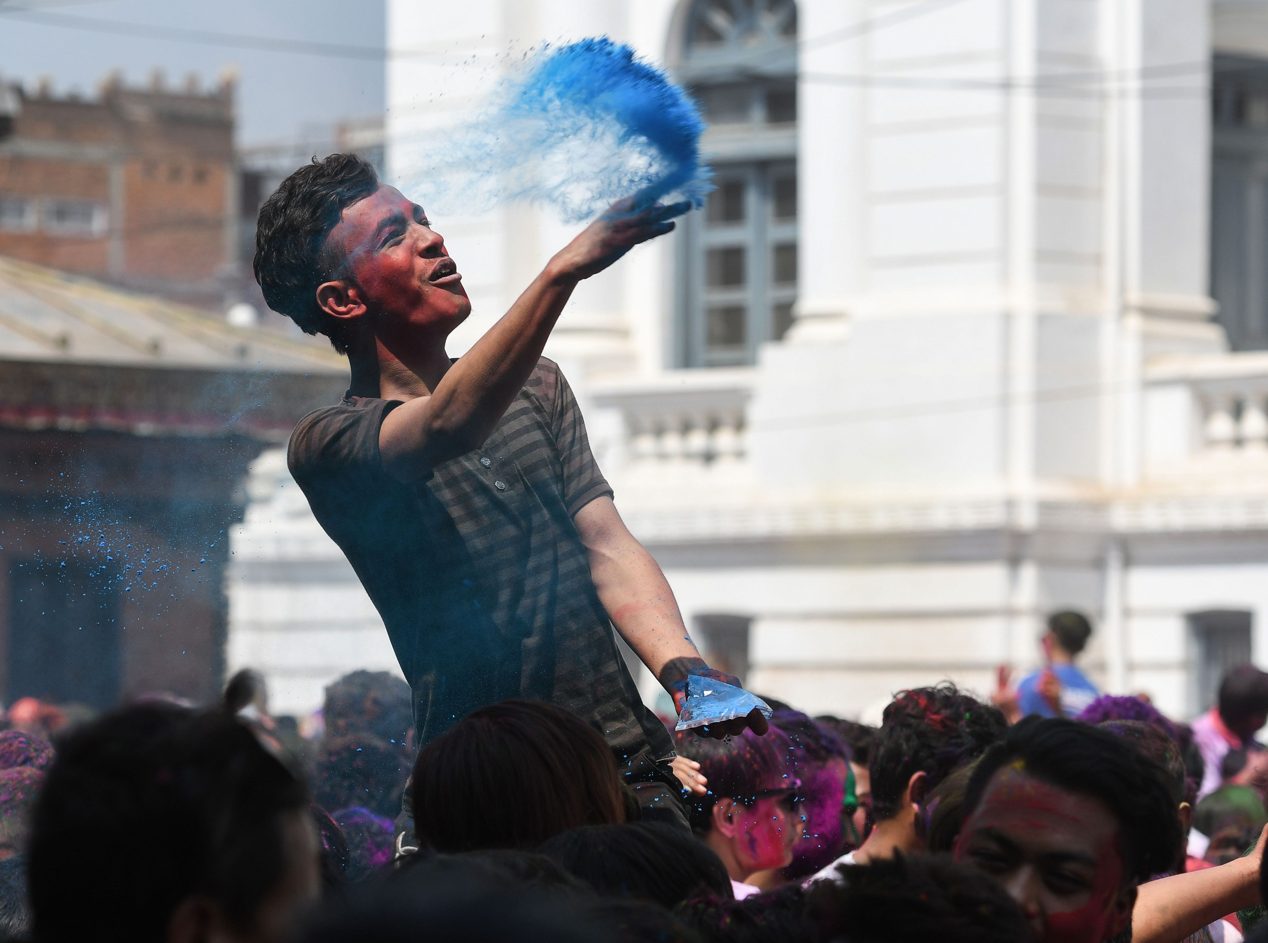 A Nepali reveler throws colored powder during the celebration of the Holi festival in Kathmandu on March 20, 2019.