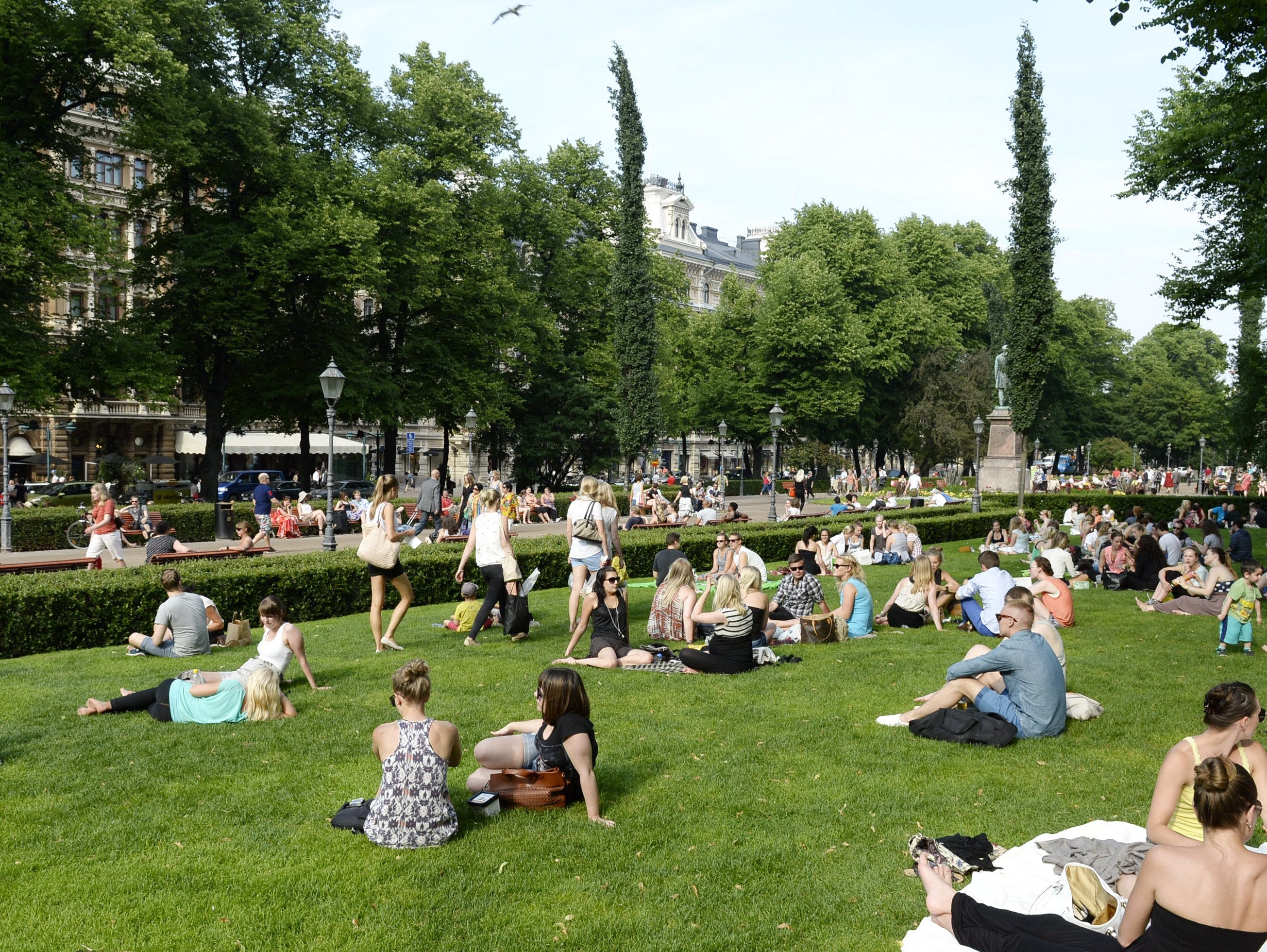 In this June 26, 2013 photo, people cool off on a hot summer day in Esplanade Park in Helsinki, Finland. In summer, glorious sun-filled days draw picnickers to every available last patch of grass. (AP Photo/Lehtikuva, Martti Kainulainen) FINLAND OUT ORG XMIT: HEL102