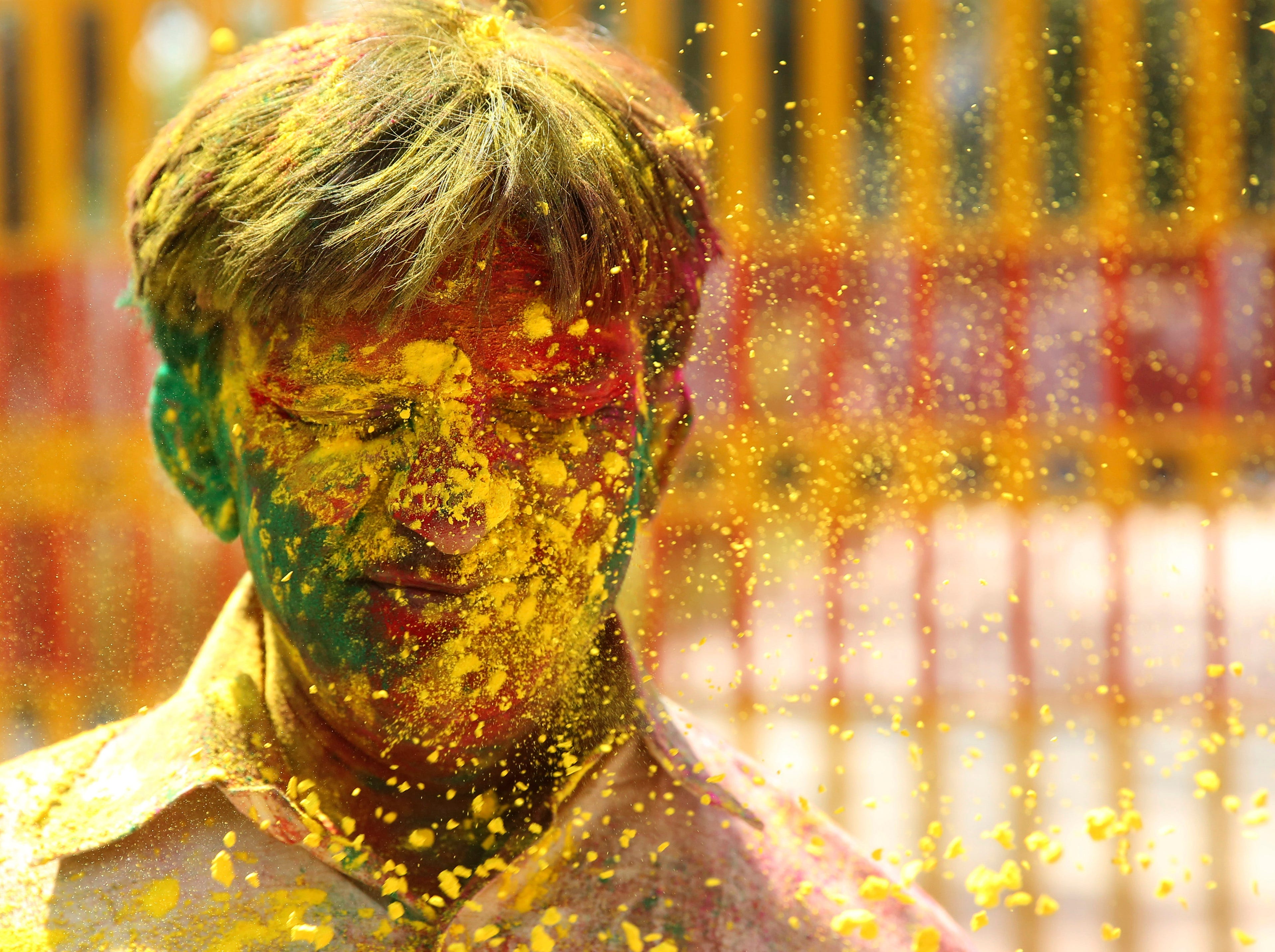 An Indian man has colored powder thrown on his face during celebrations marking Holi, the Hindu festival of colors, in Allahabad, India, Wednesday, March 20, 2019. Holi also marks the advent of spring season.