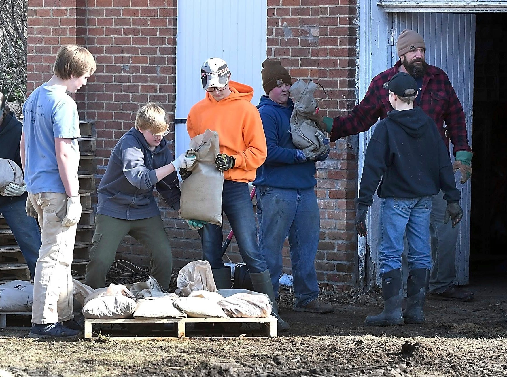 Students and teachers from Minnesota New Country School in Henderson, Minn., help stack sandbags on a pallet Wednesday, March 20, 2019.