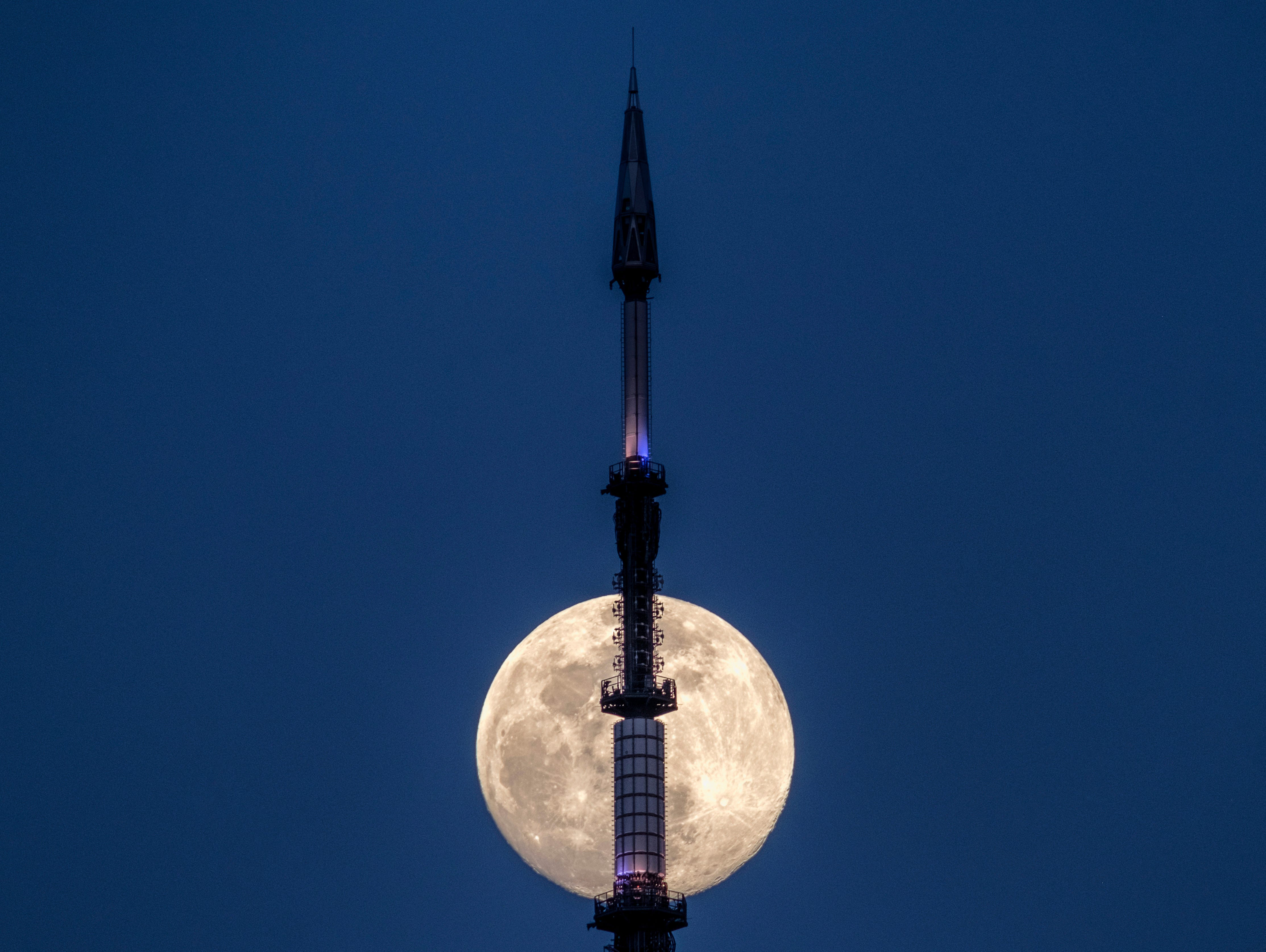 The rising moon passes behind the broadcast antenna on top of One World Trade Center Tuesday evening, March 19, 2019 in New York City.