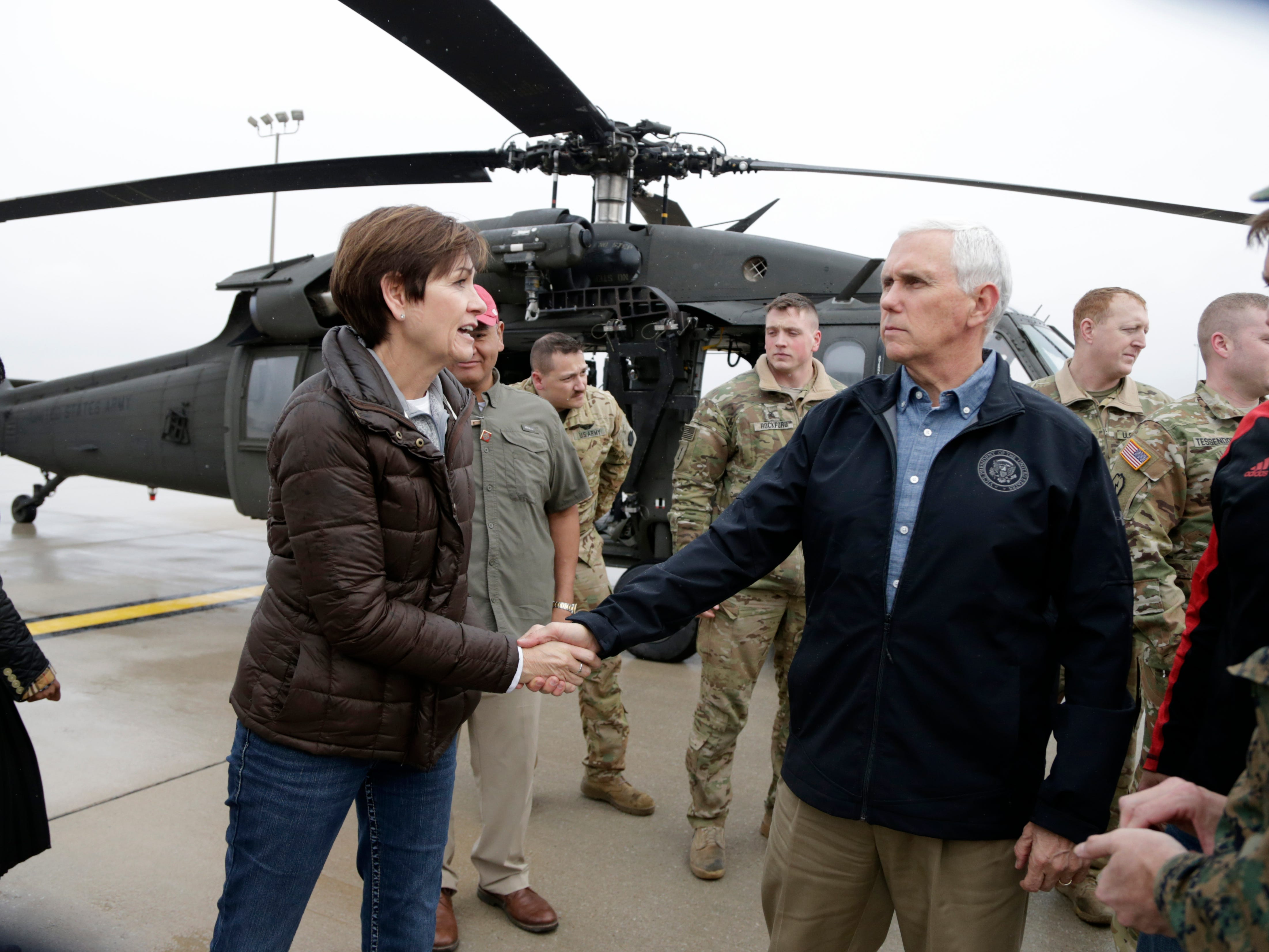 Iowa Gov. Kim Reynolds shakes Vice President Mike Pence's hand in Omaha, Neb. on, March 19, 2019, after they toured by helicopter areas flooded by the Missouri River.