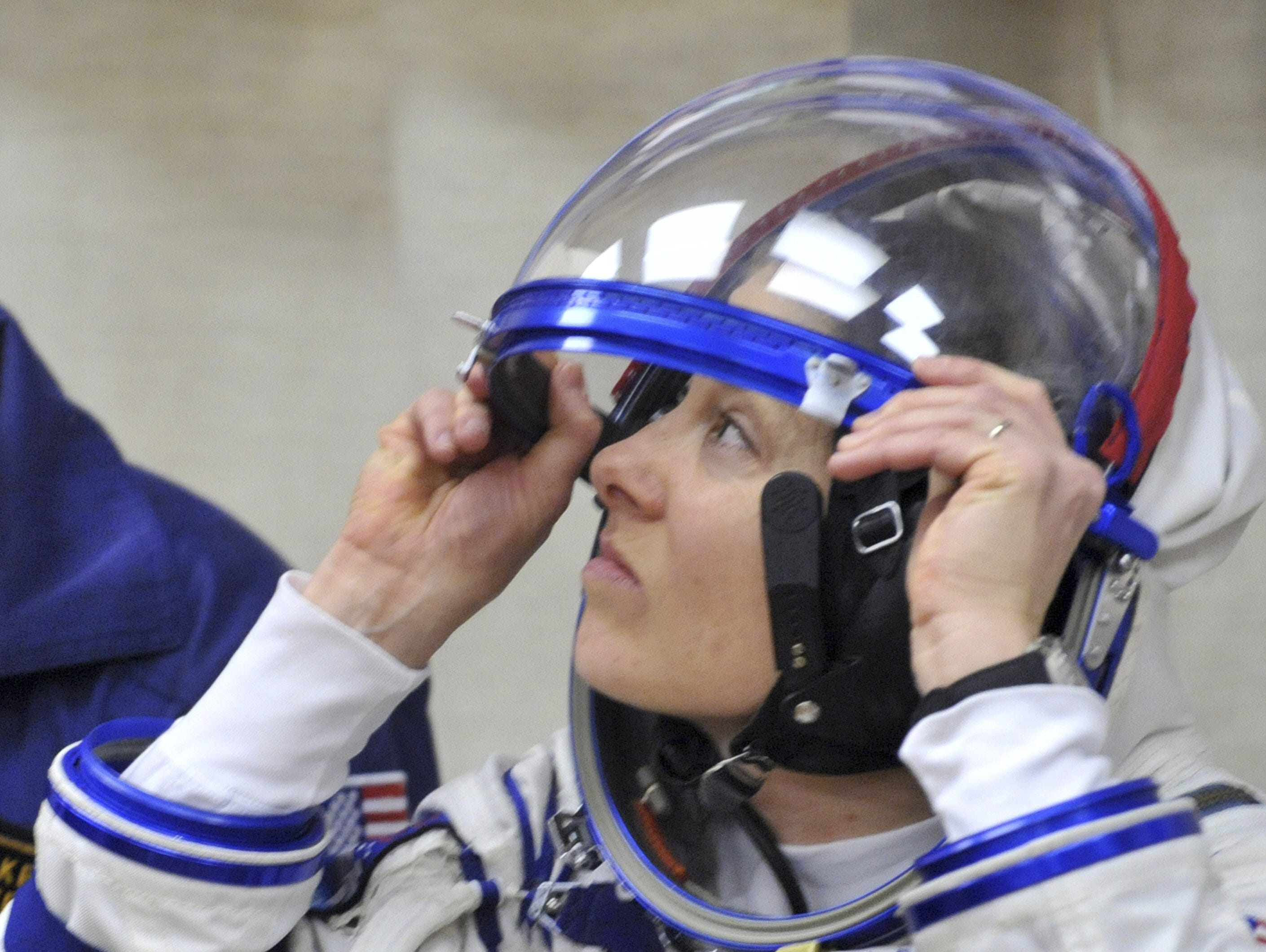 Astronaut Tracy Caldwell Dyson adjusts her helmet while getting into her space suit at Kazakhstan's Russian-leased