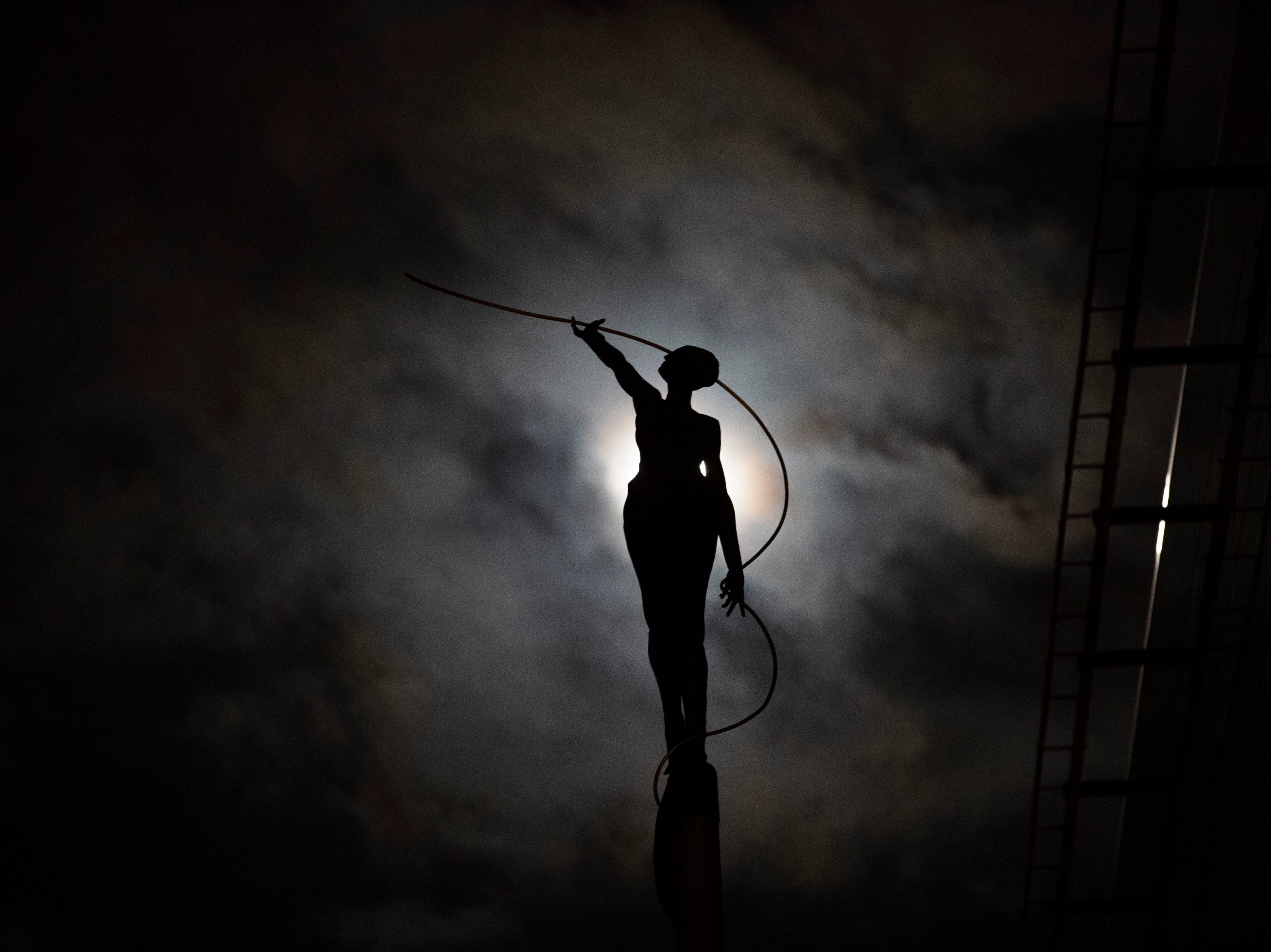 A sculpture is silhouetted against a full moon in Brussels, Wednesday, March 20, 2019.