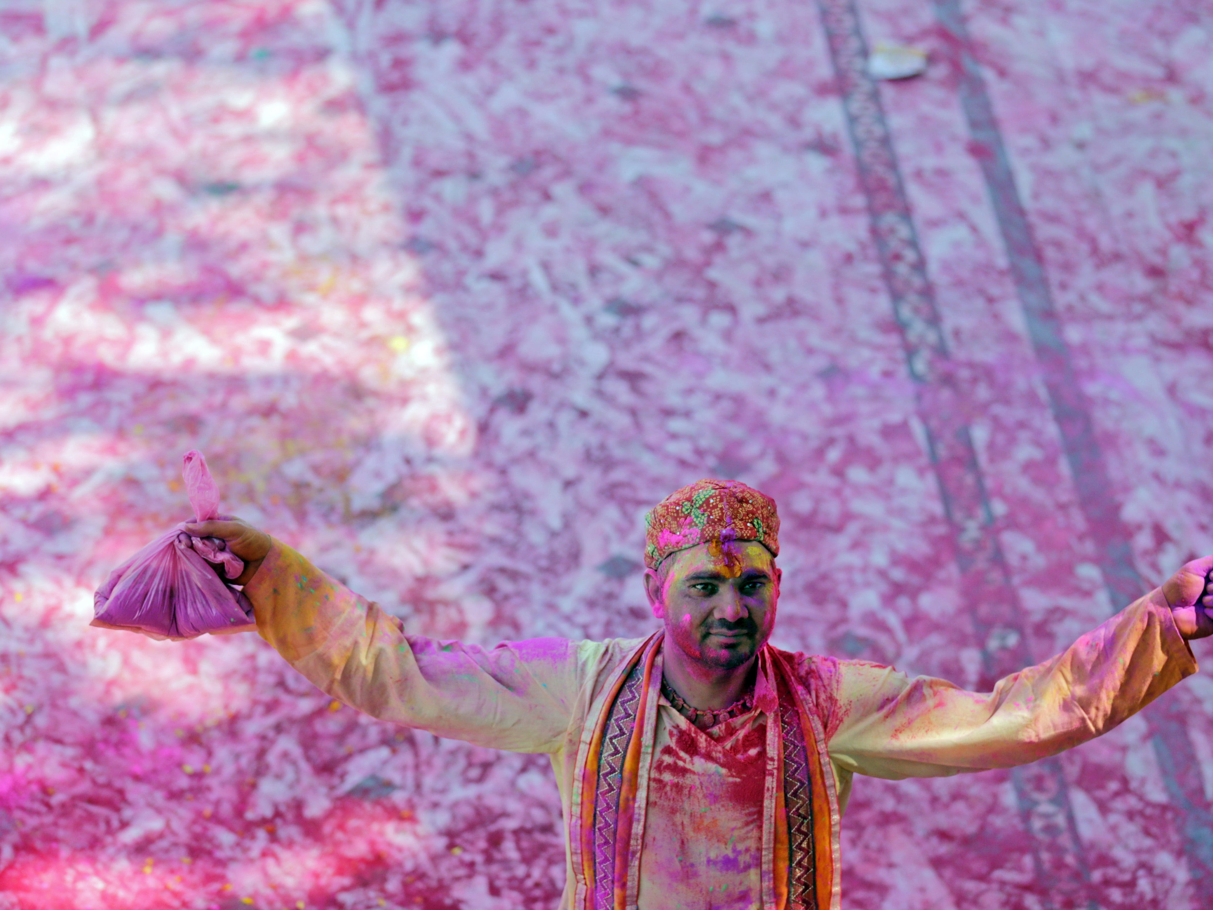 A Hindu priest is smeared with colors during Holi festival celebrations at Durgiana Temple in Amritsar, India on March 20, 2019.