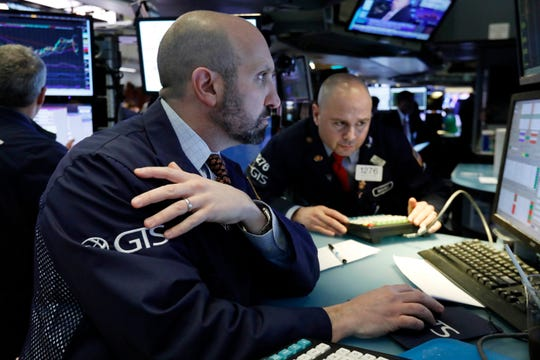 Specialists James Denaro, left, and Mario Picone work at a post on the floor of the New York Stock Exchange on March 12, 2019.