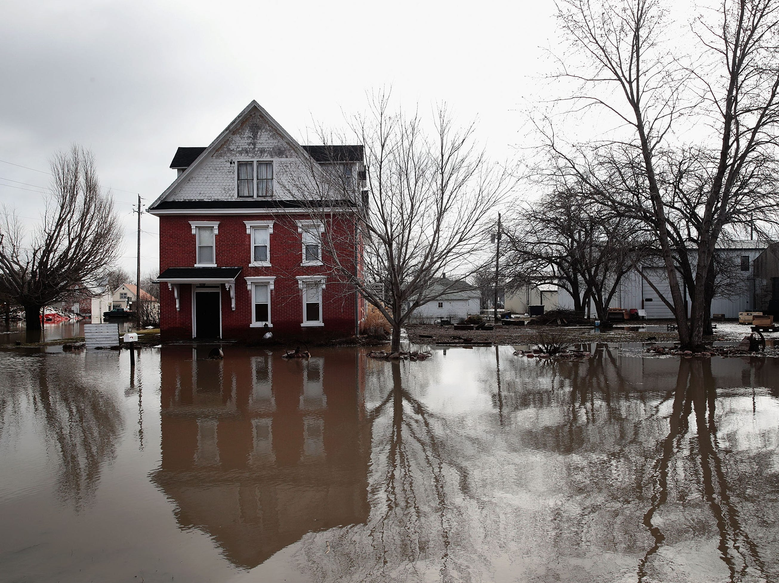 A home sits in flood water on March 20, 2019 in Hamburg, Iowa. Although flood water in the town has started to recede many homes and businesses remain surrounded by water.