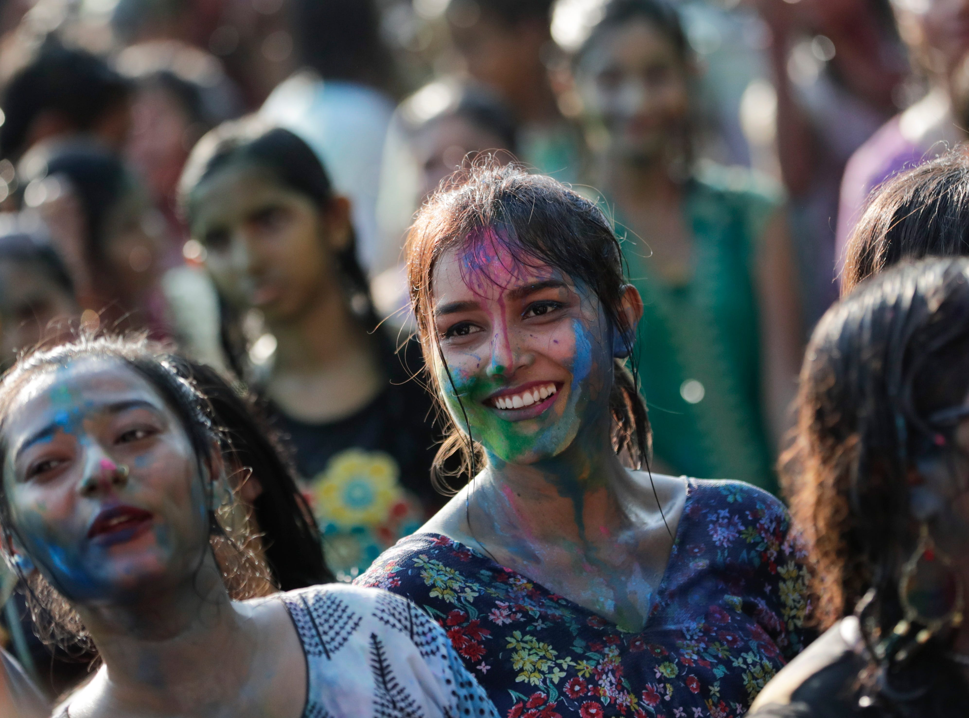 Hindu girls with faces smeared with colored powder take part of the Holi festival celebrations in Yangon, Myanmar on March 20, 2019. Holi is celebrated at the end of the winter season on the last full moon day of the lunar month Phalguna in Hindu calendar which usually falls in the later part of February or March and is celebrated by people throwing colored powder and colored water at each other.