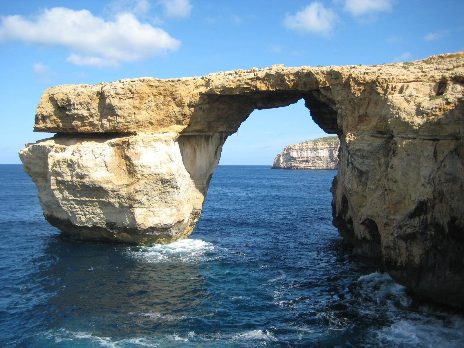 """This is a April 2014 image of the landmark the Azure Window located just off Malta.  The natural rock arch jutting off the Maltese island of Gozo, has collapsed into the sea during a storm. Malta's prime minister called the loss on Wednesday March 8, 2017, of the iconic limestone formation """"heartbreaking."""" No one was injured by the fallen arch, which was also a TV and film backdrop.(Caroline Hodgson via AP) ORG XMIT: LON830"""