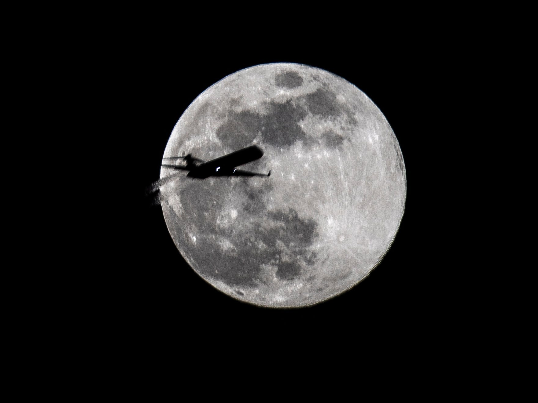 A plane passes in front of the 'Super Worm Moon' reaching its peak on the first day of spring in Frankfurt am Main, Germany on March 20, 2019. Its name comes from northern Native American tribes that said this moon signaled the thawing of winter snow and the reappearance of earthworms in the soil.