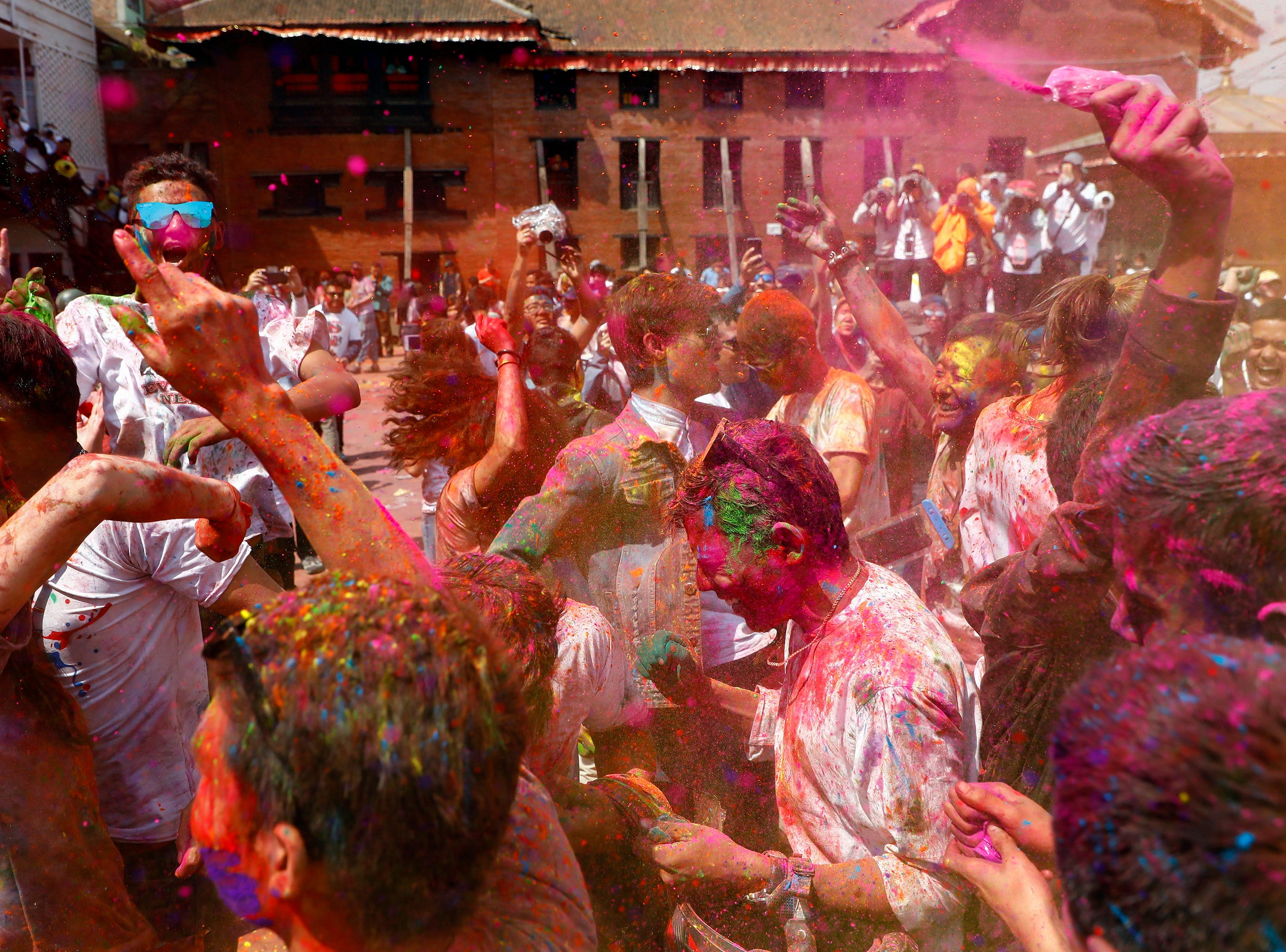 Nepalese people painted with colored powder dance during Holi Festival celebrations in Kathmandu, Nepal on March 20, 2019. Holi, also known as the Festival of Colors, marks the beginning of spring and is celebrated all over Nepal and neighboring India.