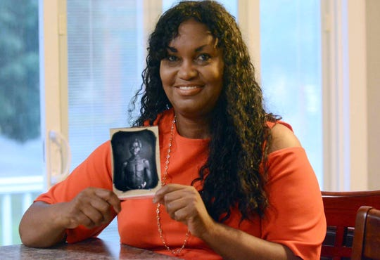 In this July 17, 2018, photo, Tamara Lanier holds an 1850 photograph of Renty, a South Carolina slave who Lanier said is her family's patriarch, at her home in Norwich, Connecticut.