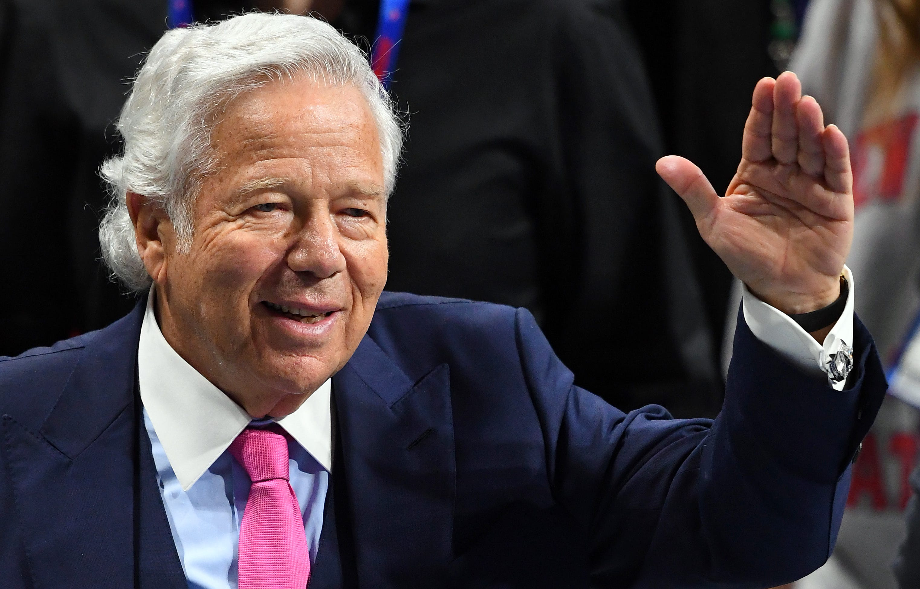 Robert Kraft gestures to fans as he walks down the sidelines before Super Bowl LIII.